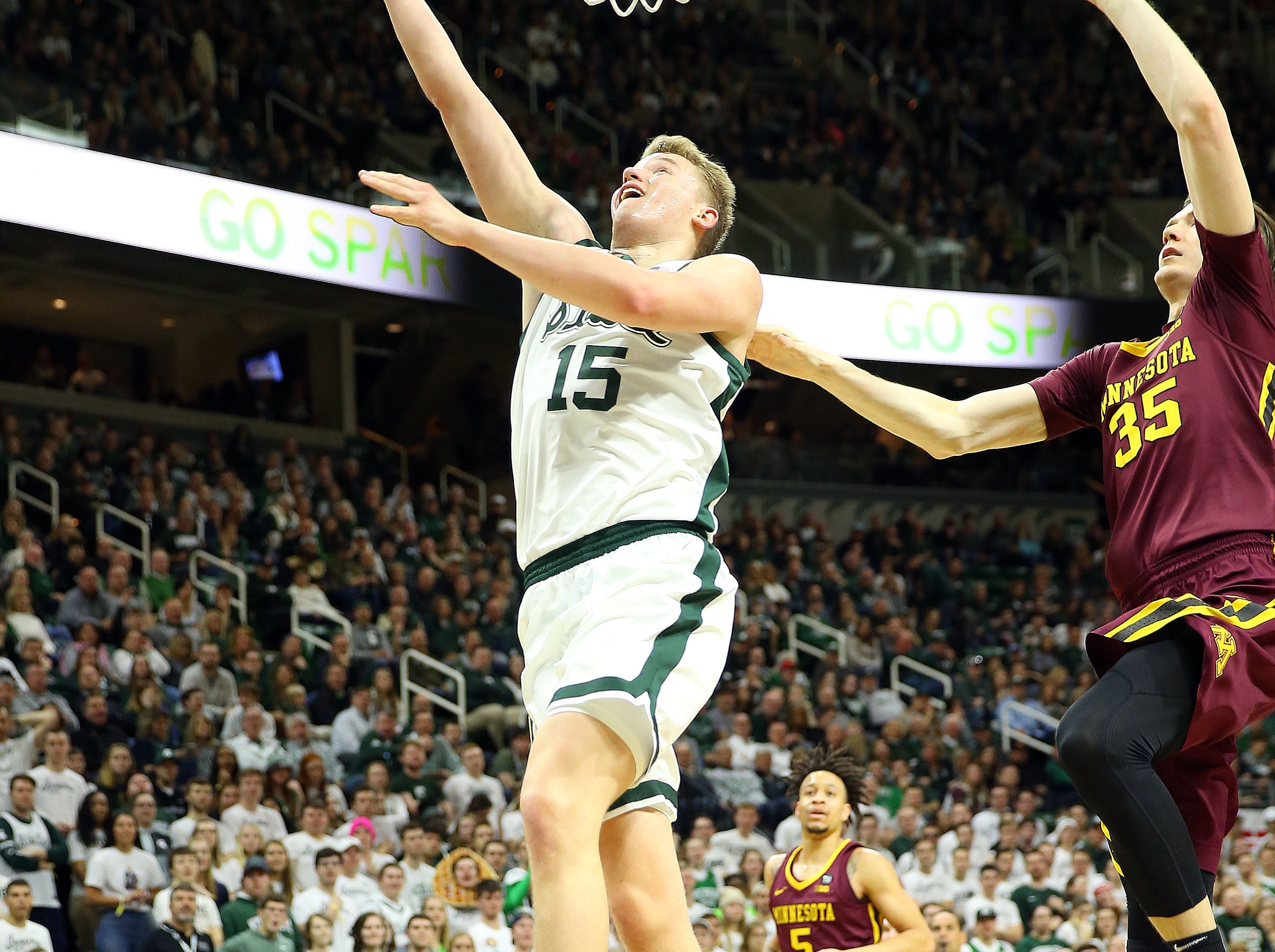 Feb 9, 2019; East Lansing, MI, USA; Michigan State Spartans forward Thomas Kithier (15) lays the ball up against Minnesota Golden Gophers center Matz Stockman (35) during the second half at the Breslin Center. Mandatory Credit: Mike Carter-USA TODAY Sports