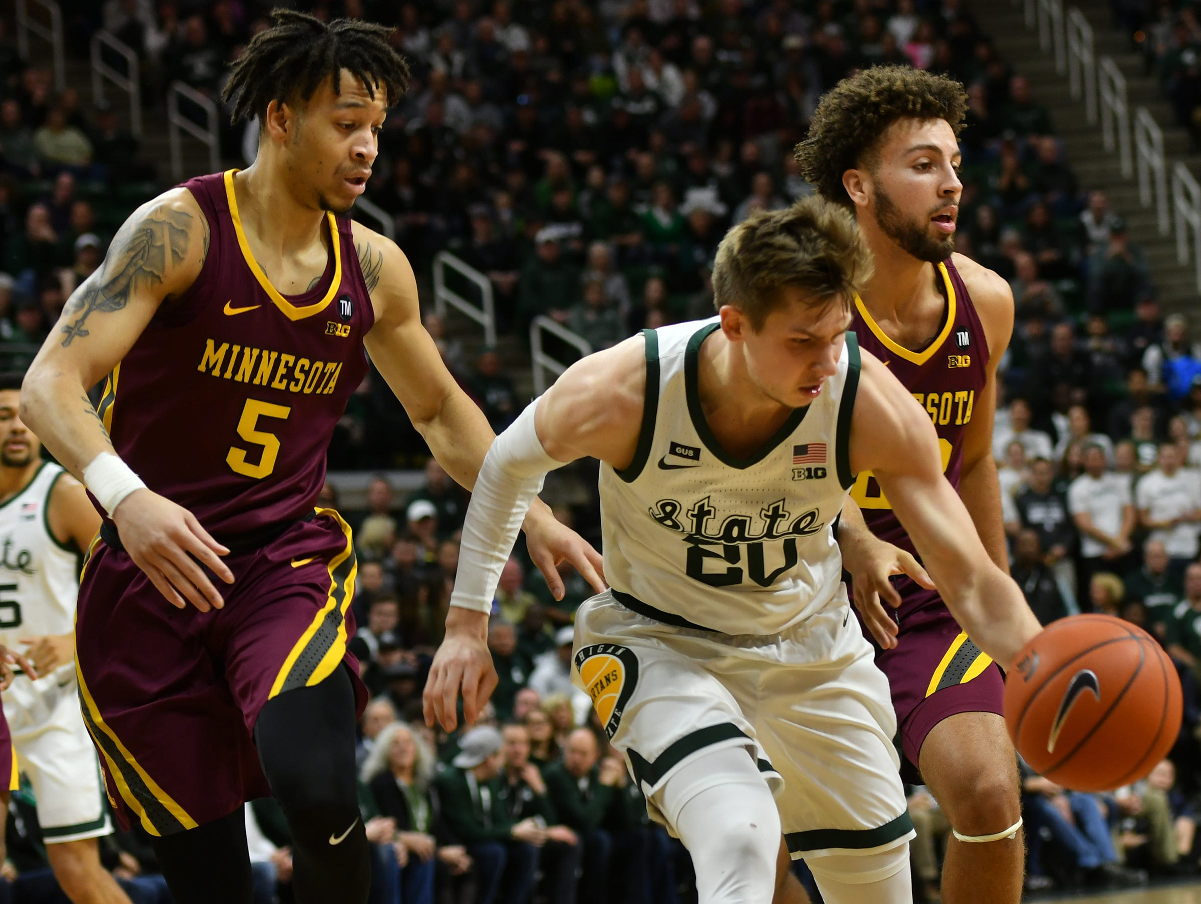MSU's Matt McQuaid (20) works his way around Minnesota's Amir Coffey (5) Saturday, Feb. 9, 2019. MSU won 79-55.