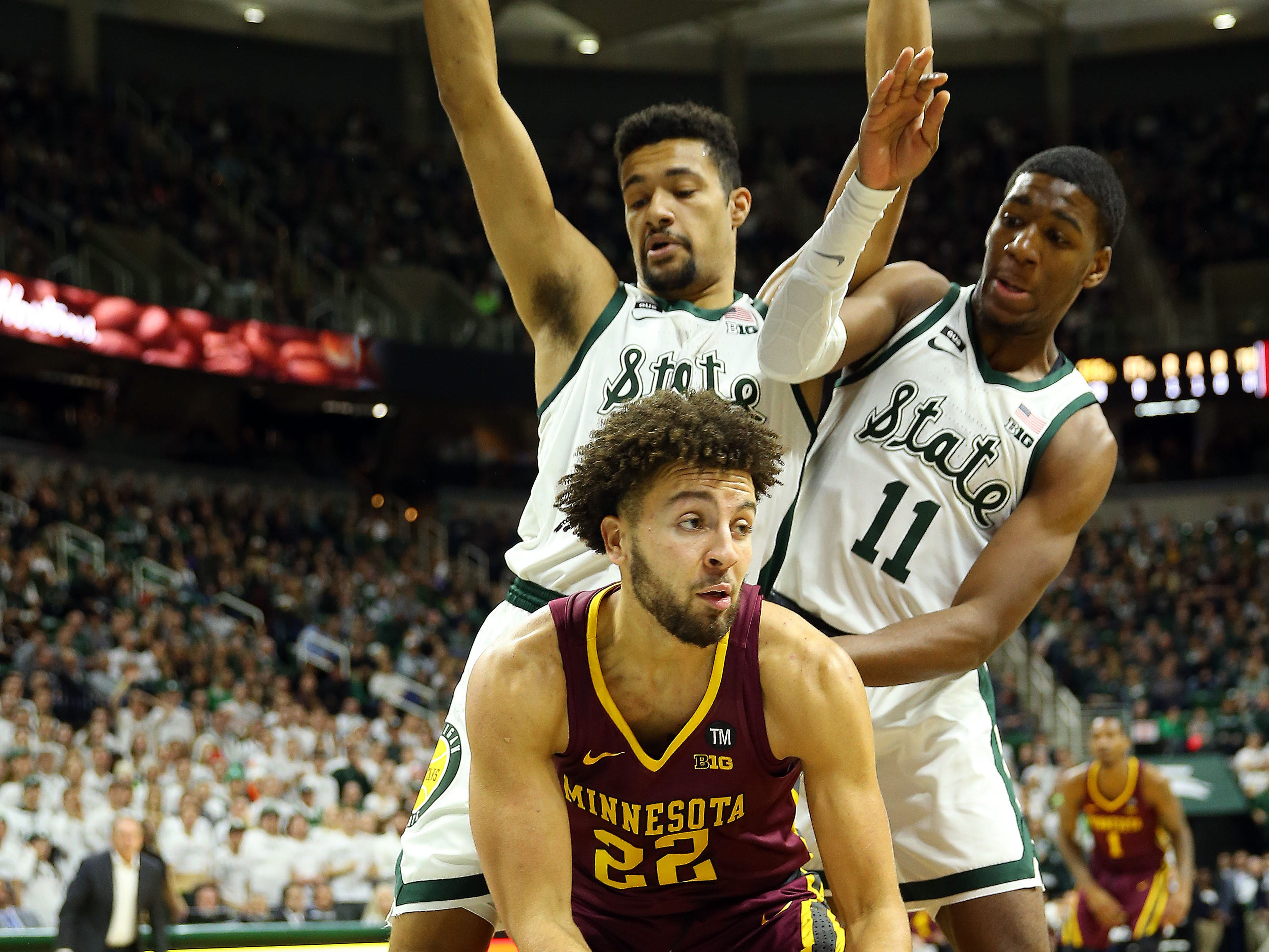Feb 9, 2019; East Lansing, MI, USA; Minnesota Golden Gophers guard Gabe Kalscheur (22) dribbles against Michigan State Spartans forward Kenny Goins (25) and forward Aaron Henry (11) during the first half at the Breslin Center. Mandatory Credit: Mike Carter-USA TODAY Sports