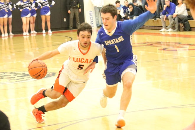 Lucas' Ethan Sauder drives by St. Peter's Eli Gurski during the Cubs' victory on Friday night to net them their first Mid-Buckeye Conference championship since 1991.