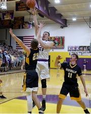 Nick Stehle of Lexington shoots the ball over Norwalk's Ian Minor and Garrett Obringer on Friday night at Lexington High School.