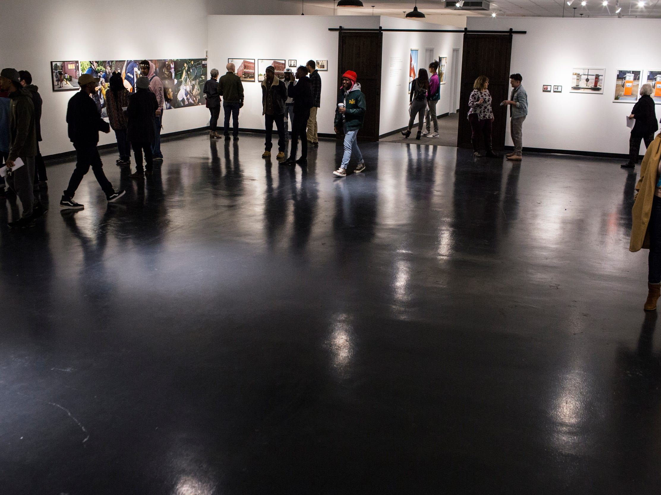 February 08, 2019 - People check out local artists work during the PHTGRPHS show featuring work by Lester Merriweather and Lawrence Matthews at The CMPLX. The CMPLX, a gallery, office, and work space for The Collective, is located at 2234 Lamar Ave. in the Lamar Airways Shopping Center in Orange Mound.