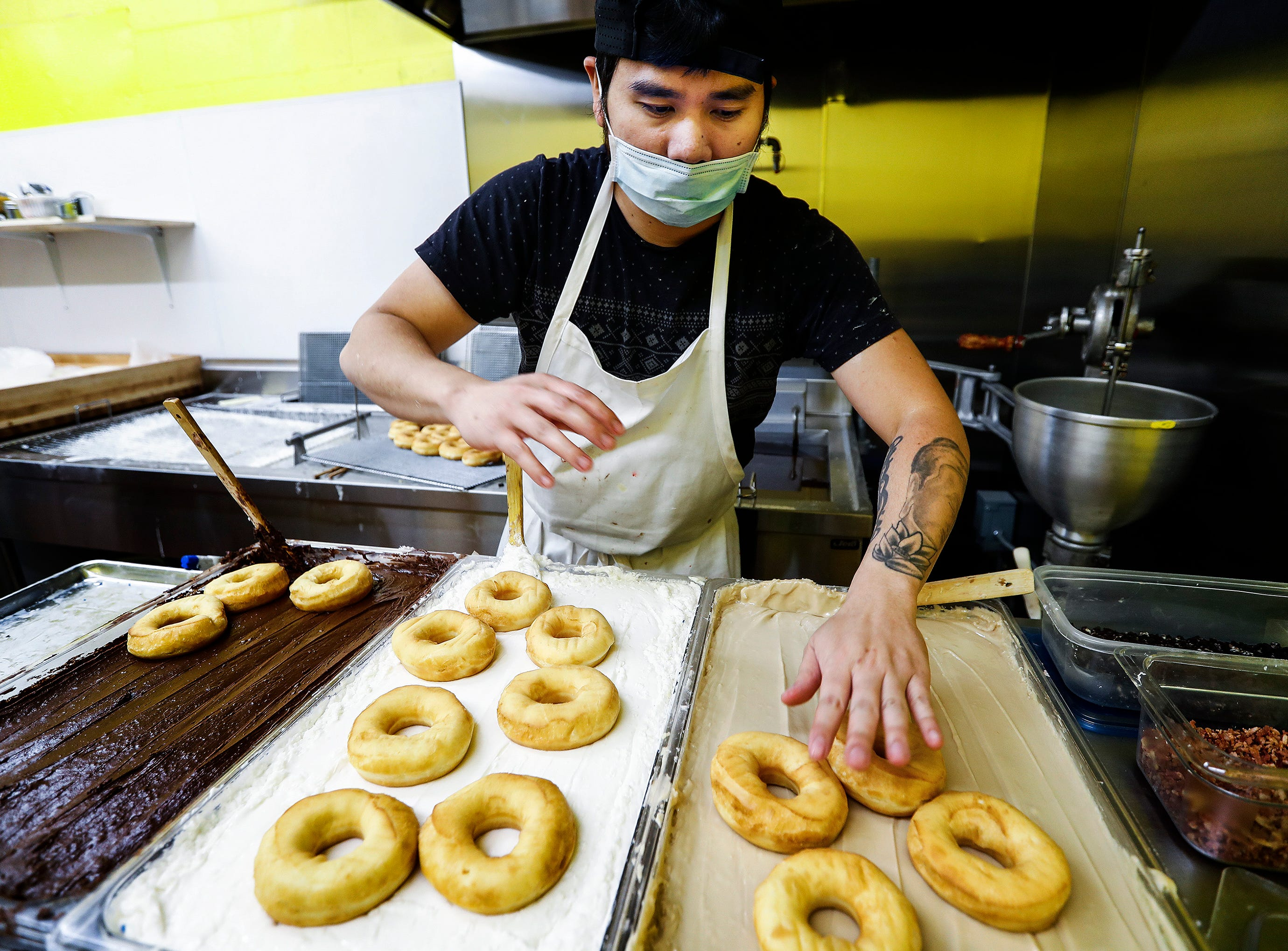 KP Phat glazes doughnuts during the grand opening of Midtown Donut on Union Ave., Saturday morning. Midtown Donuts will offer a selection of coffees, including brewed coffee and cappuccinos. The doughnut shop will be open seven days a week from 4 a.m. to 7 p.m.