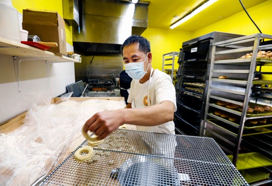 Owner Ly Touch makes doughnuts during the grand opening of Midtown Donut on Union Ave., Saturday morning. Midtown Donuts will offer a selection of coffees, including brewed coffee and cappuccinos. The doughnut shop will be open seven days a week from 4 a.m. to 7 p.m.