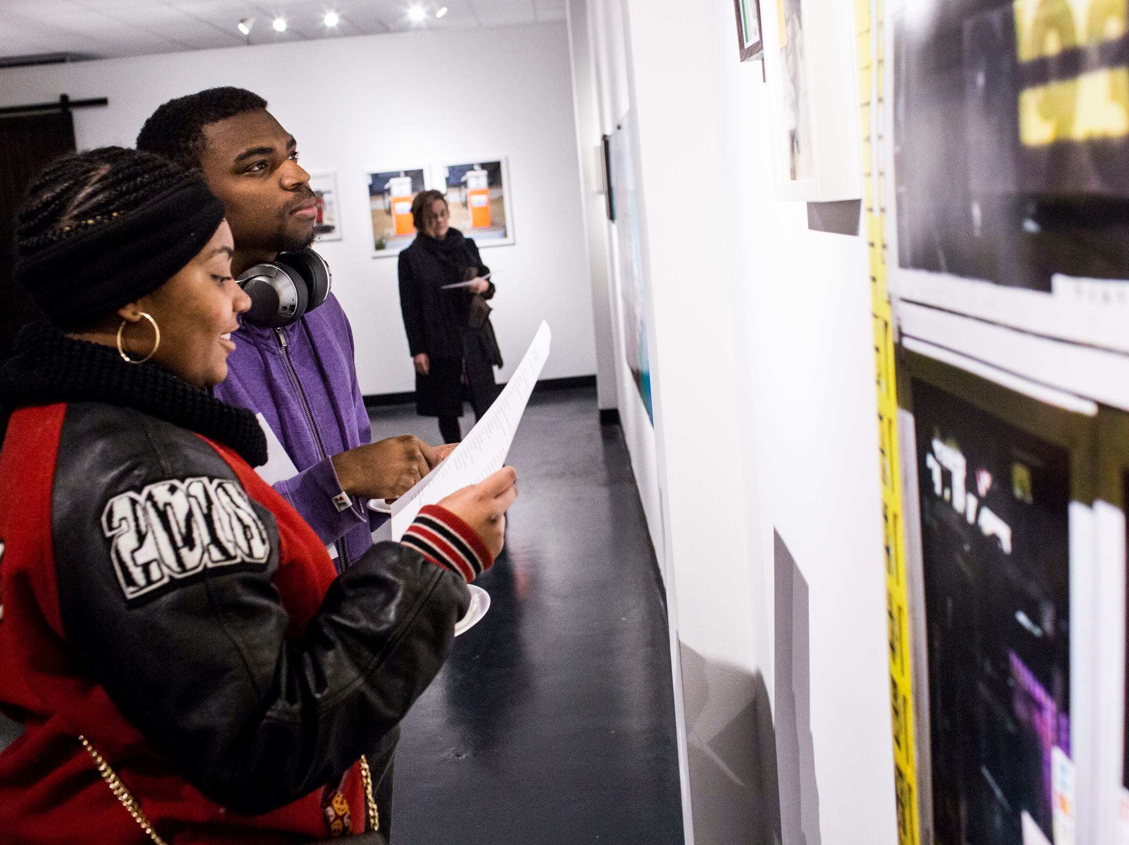 February 08, 2019 - Cheryiah Hill, left, and Caleb Stokes, right, look at work during the PHTGRPHS show featuring work by Lester Merriweather and Lawrence Matthews at The CMPLX. The CMPLX, a gallery, office and work space for The Collective, is located at 2234 Lamar Ave. in the Lamar Airways Shopping Center in Orange Mound.