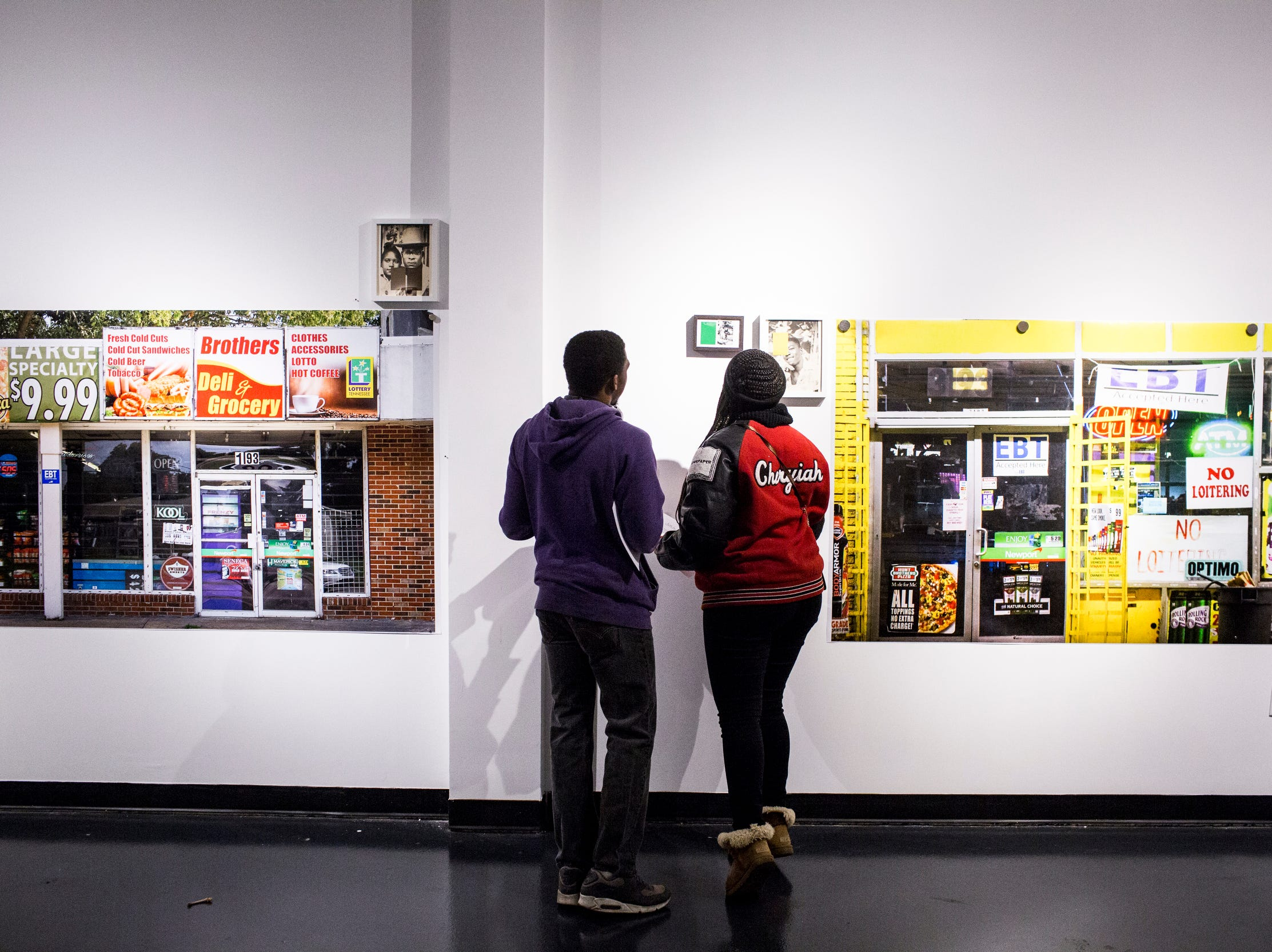 February 08, 2019 - Caleb Stokes, left, and Cheryiah Hill, right, look at work during the PHTGRPHS show featuring work by Lester Merriweather and Lawrence Matthews at The CMPLX. The CMPLX, a gallery, office and work space for The Collective, is located at 2234 Lamar Ave. in the Lamar Airways Shopping Center in Orange Mound.