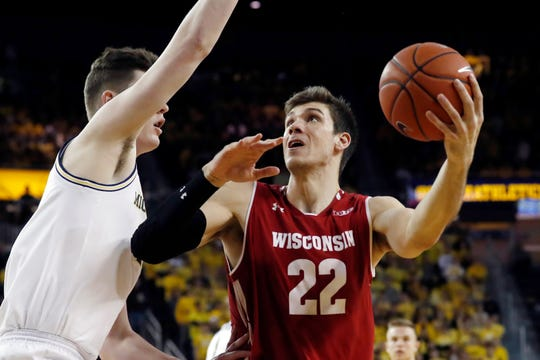 Wisconsin forward Ethan Happ tries to find space for a shot against the tight defense of Michigan center Jon Teske.