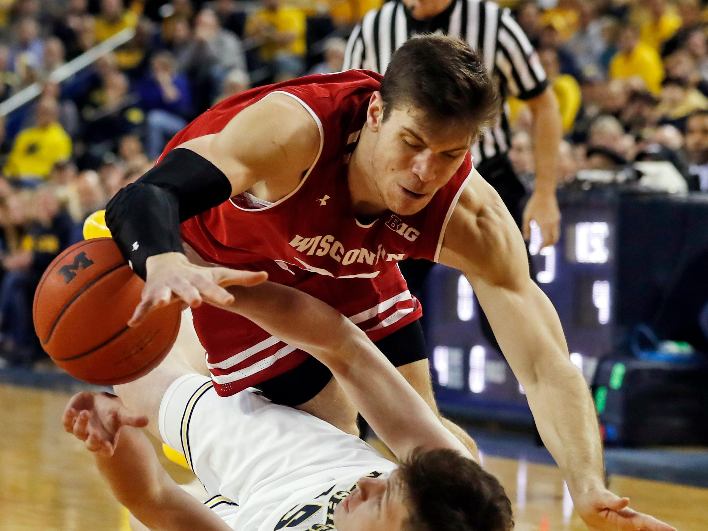 Wisconsin forward Ethan Happ, and Michigan center Jon Teske chase after a loose ball.