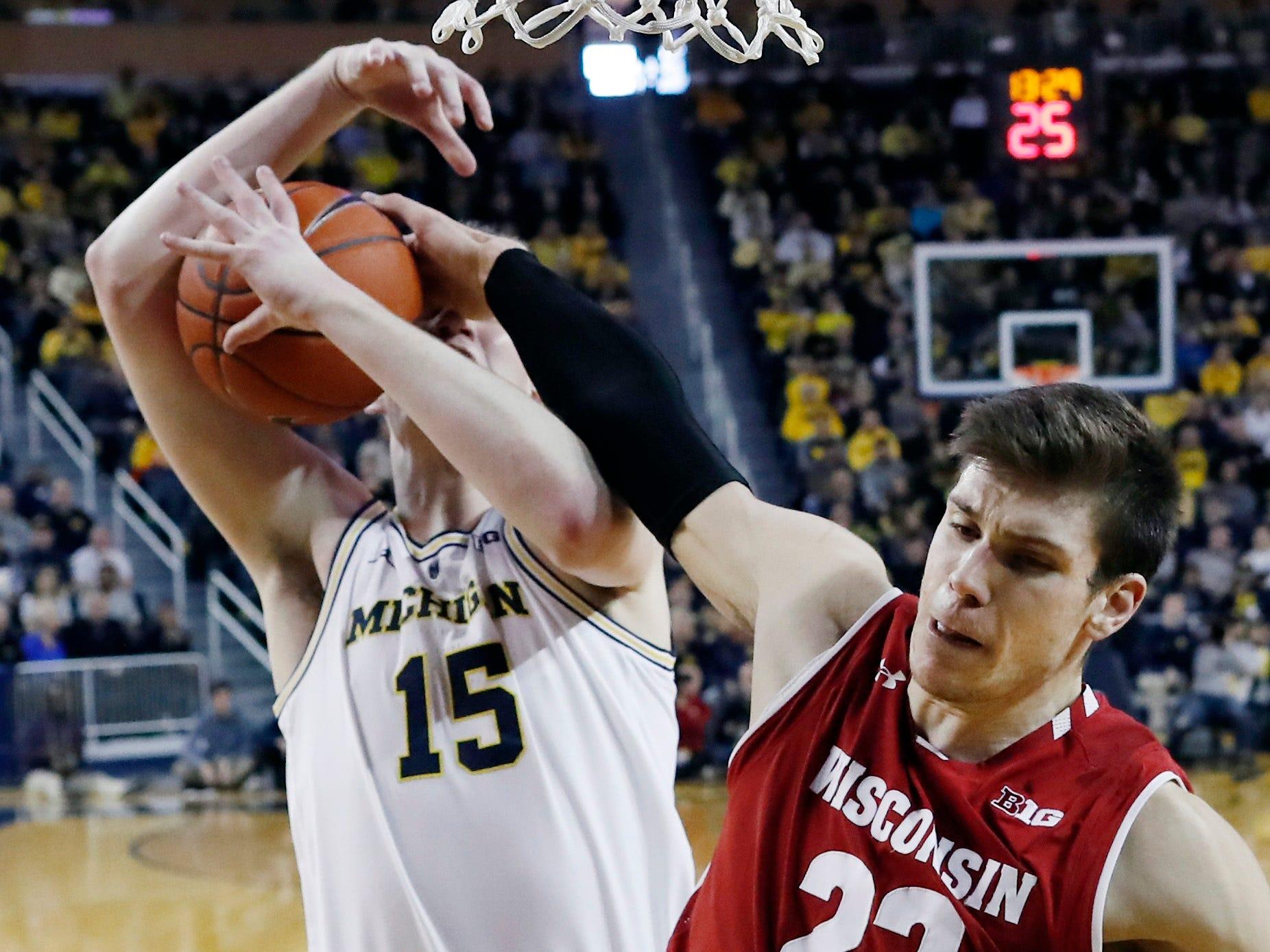 Wisconsin forward Ethan Happ knocks the ball away from Michigan center Jon Teske.