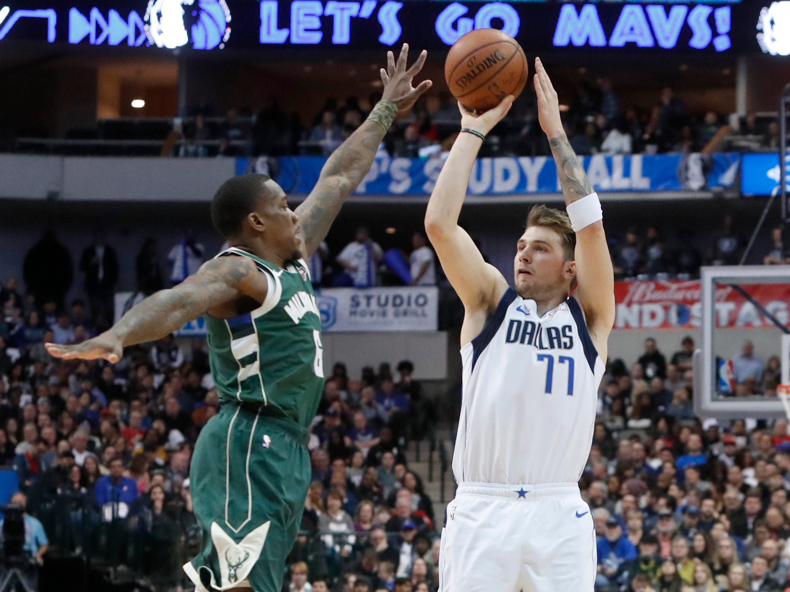 Mavericks forward Luka Doncic launches a three-pointer over Bucks guard Eric Bledsoe during the first half. Dallas tied a franchise record by hitting 22 trifectas against Milwaukee on Friday night.