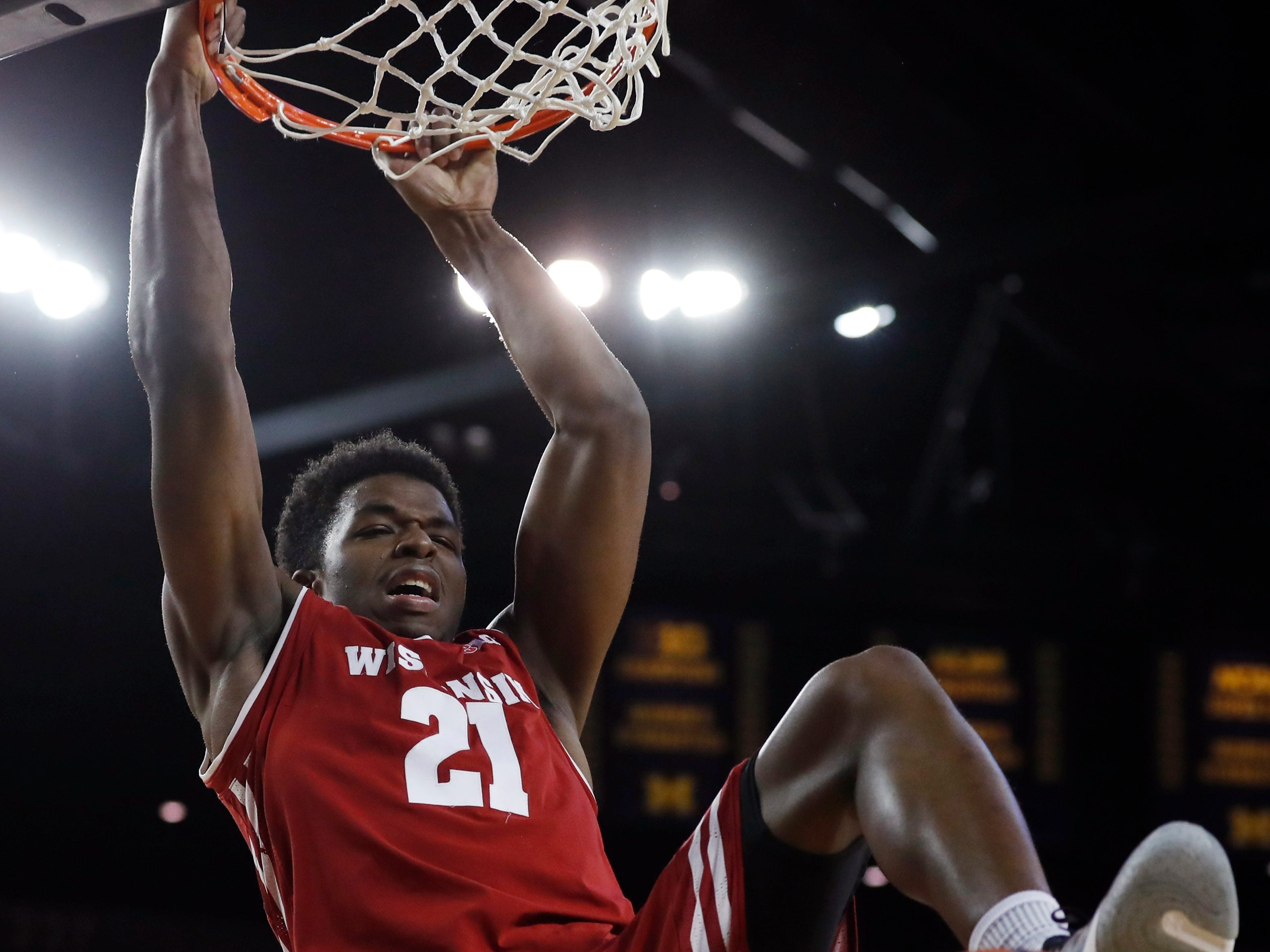 Wisconsin guard Khalil Iverson hangs on the rim after dunking during the first half  on Saturday.