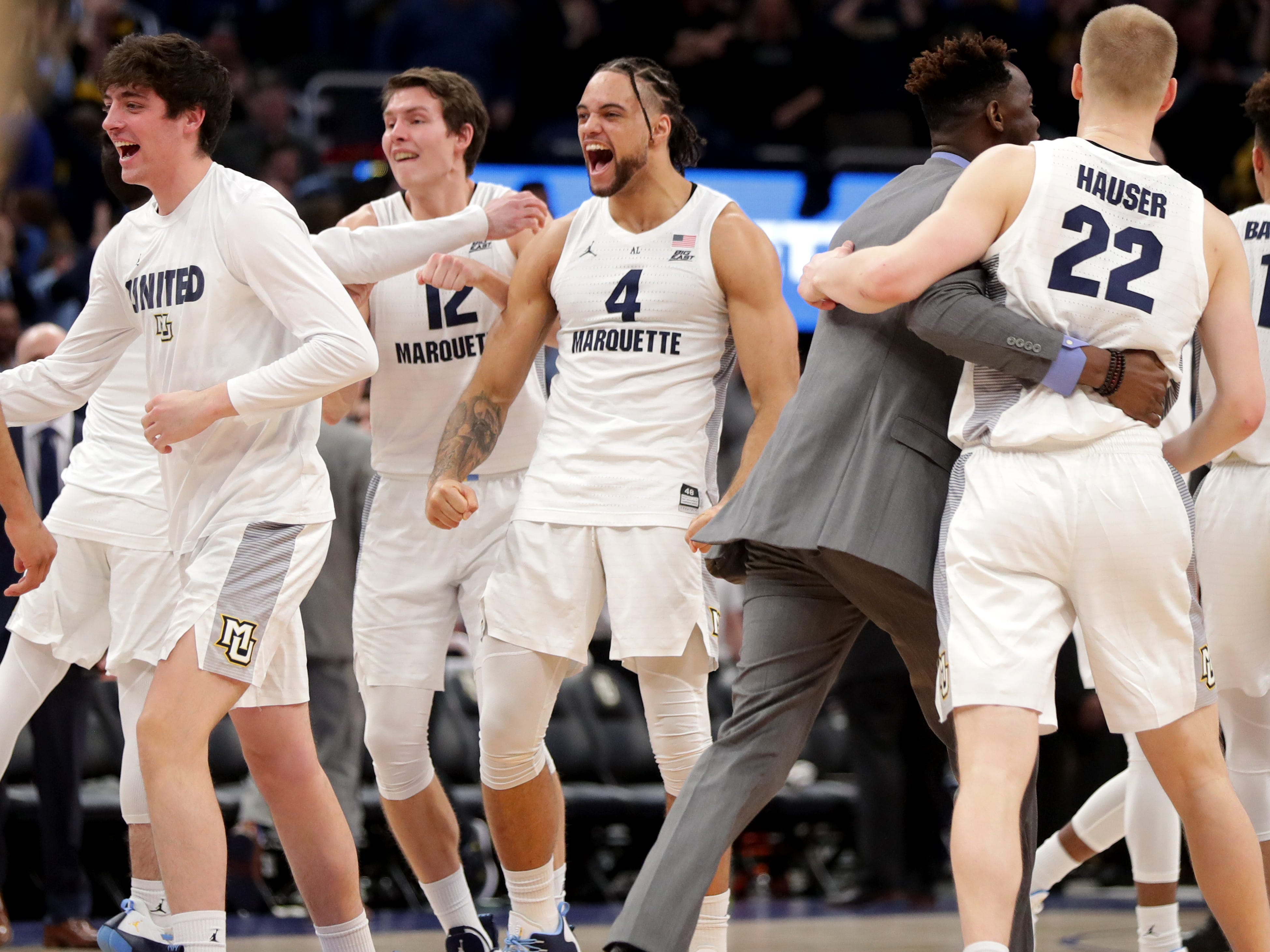 Marquette forward Theo John celebrates with his teammates after the Golden Eagles defeat Villanova on Saturday.