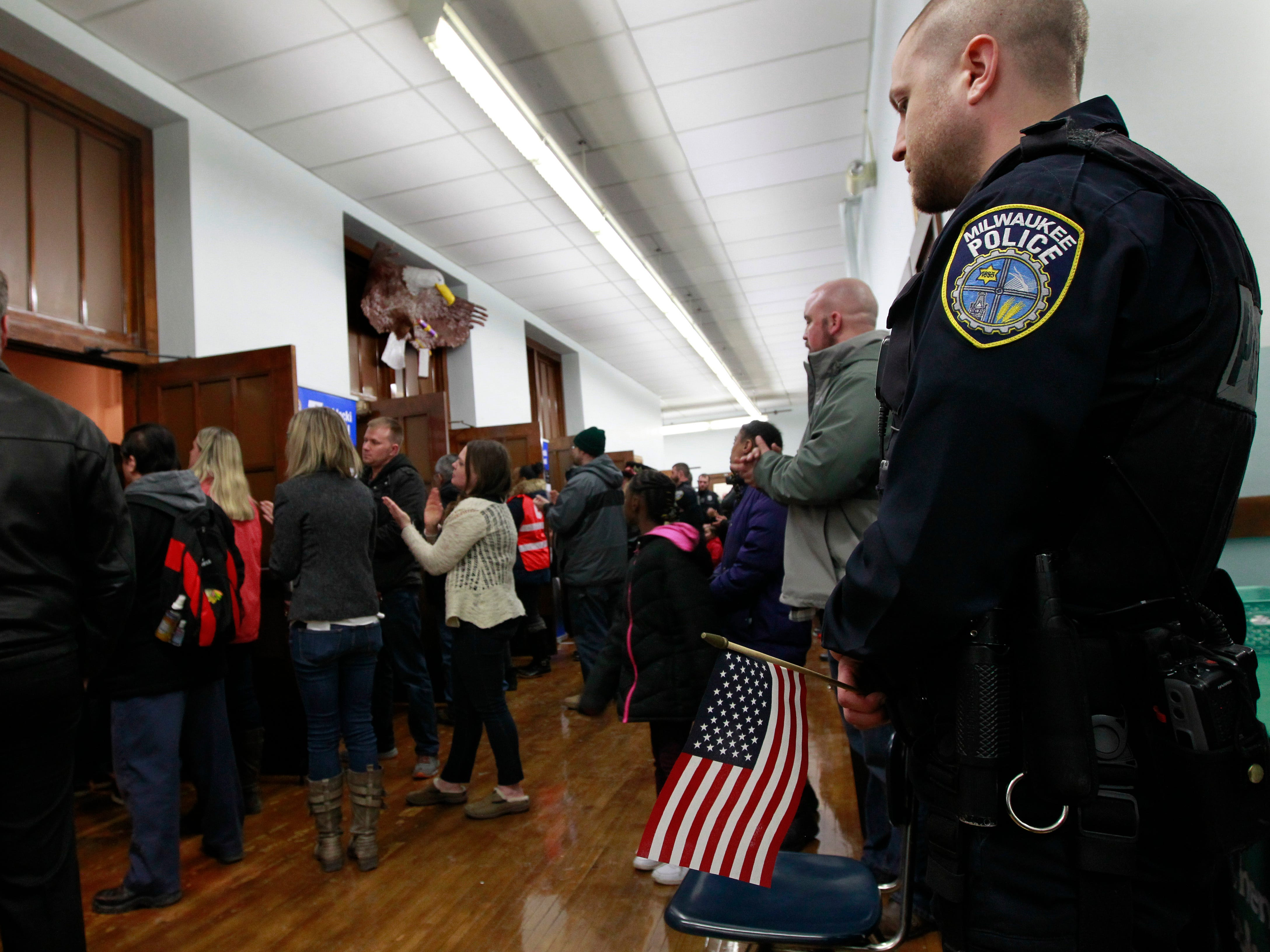 A Milwaukee police officer listens to speakers at a vigil for fallen Officer Matthew Rittner on Friday, Feb. 8, 2019, at Zablocki Elementary School. Rittner was shot while serving a search warrant on Wednesday.