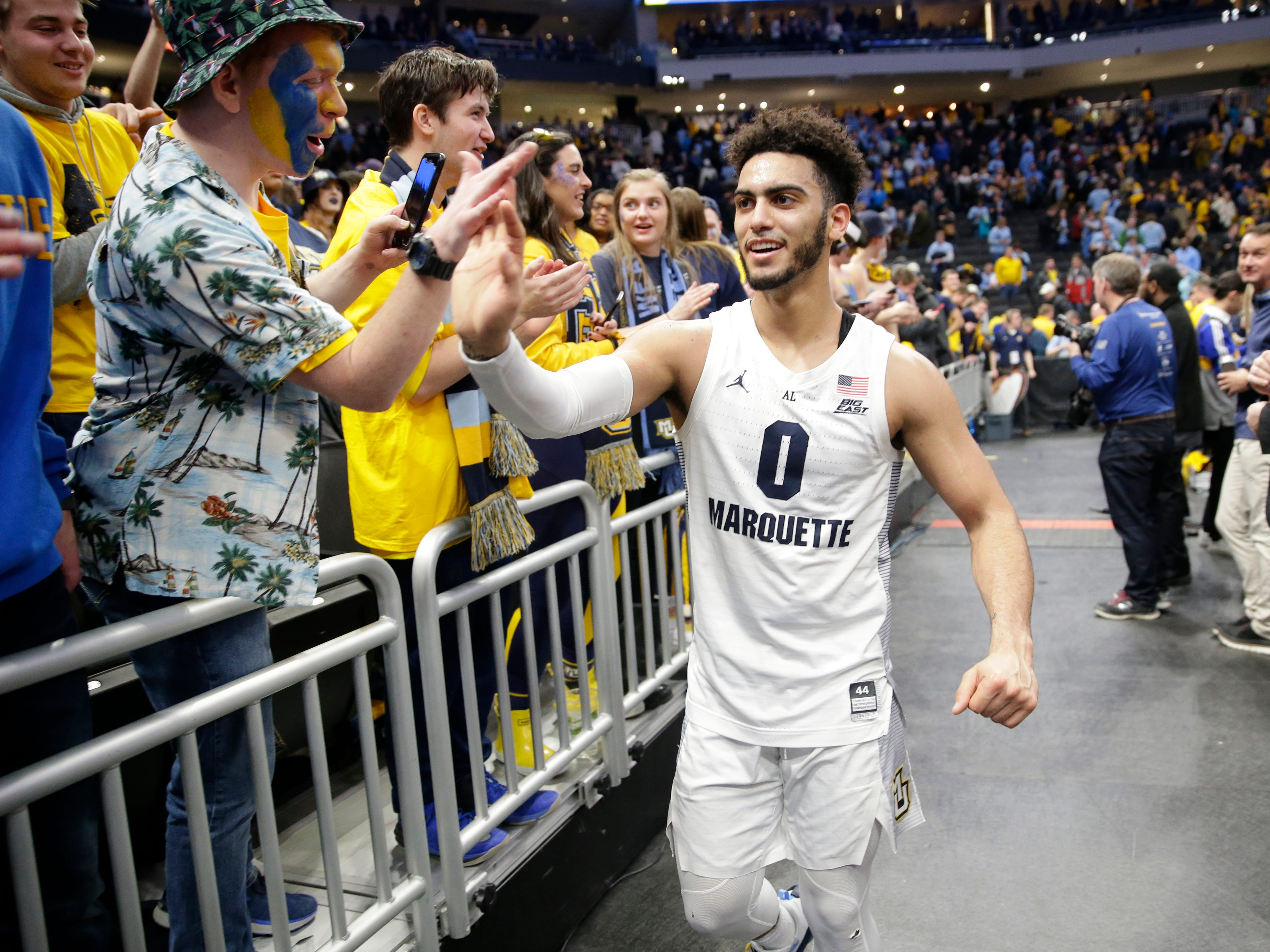 Marquette Golden Eagles guard Markus Howard celebrates with fans after Marquette's victory on Saturday.