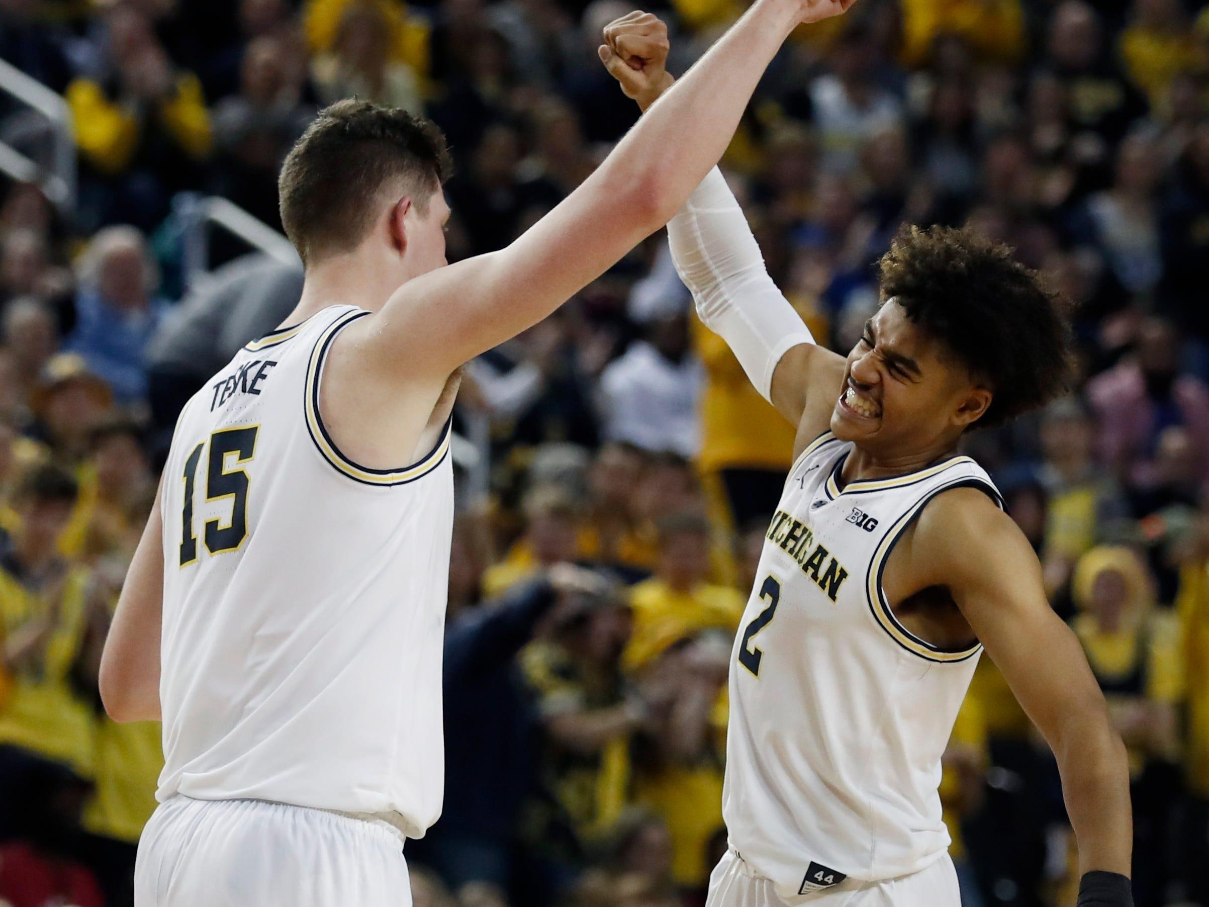 Michigan center Jon Teske (left) and guard Jordan Poole celebrate a basket in the second half.