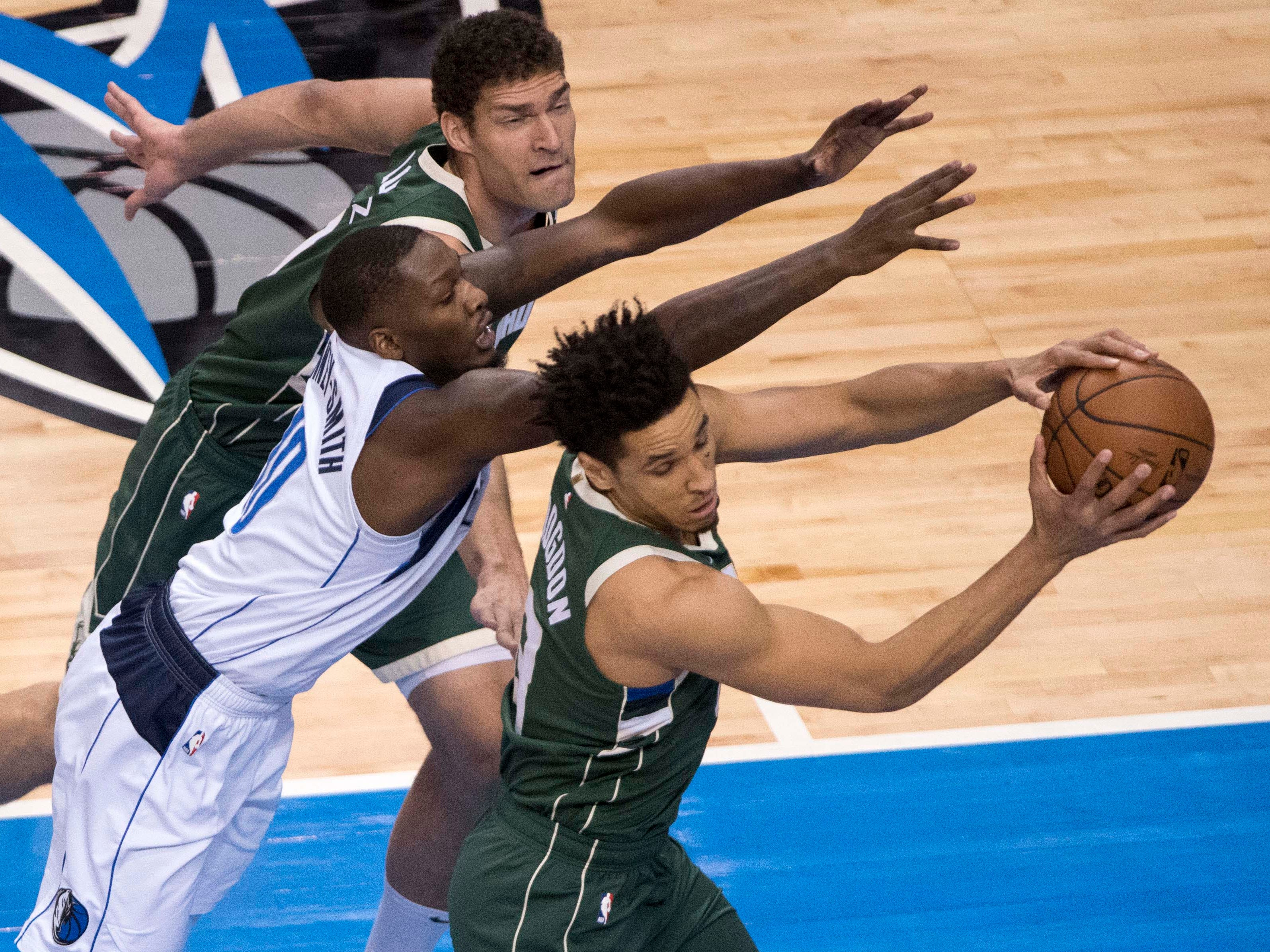 Bucks guard Malcolm Brogdon snares a rebound before Mavericks forward Dorian Finney-Smith can get to it during the first quarter Friday night.