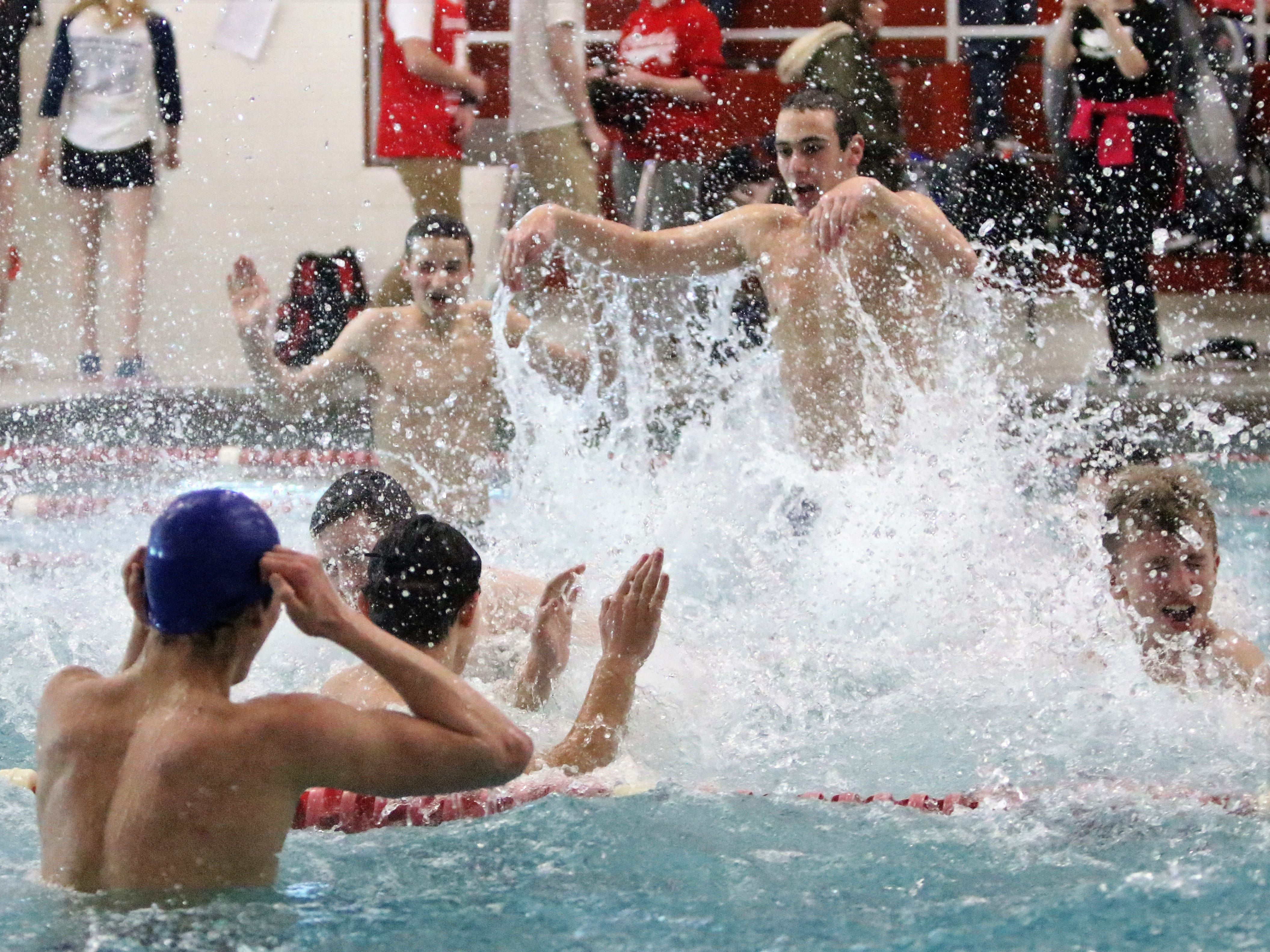 Members of the Brookfield East/Central co-op celebrate in the pool after winning the WIAA sectional meet at Homestead High School on Feb. 9, 2019.