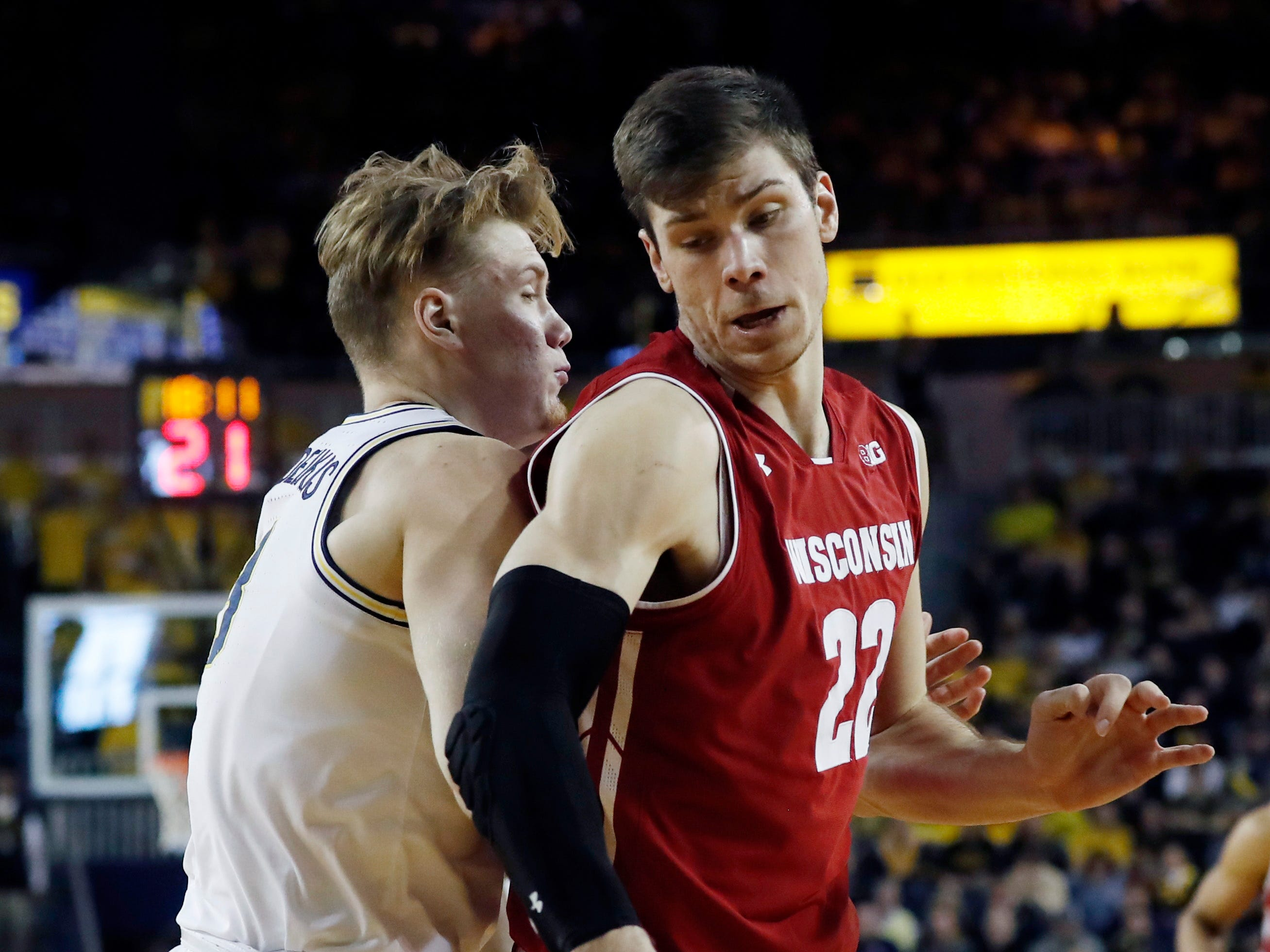 Wisconsin forward Ethan Happ dribbles around Michigan forward Ignas Brazdeikis on Saturday. Happ finished with 18 points and 11 rebounds.