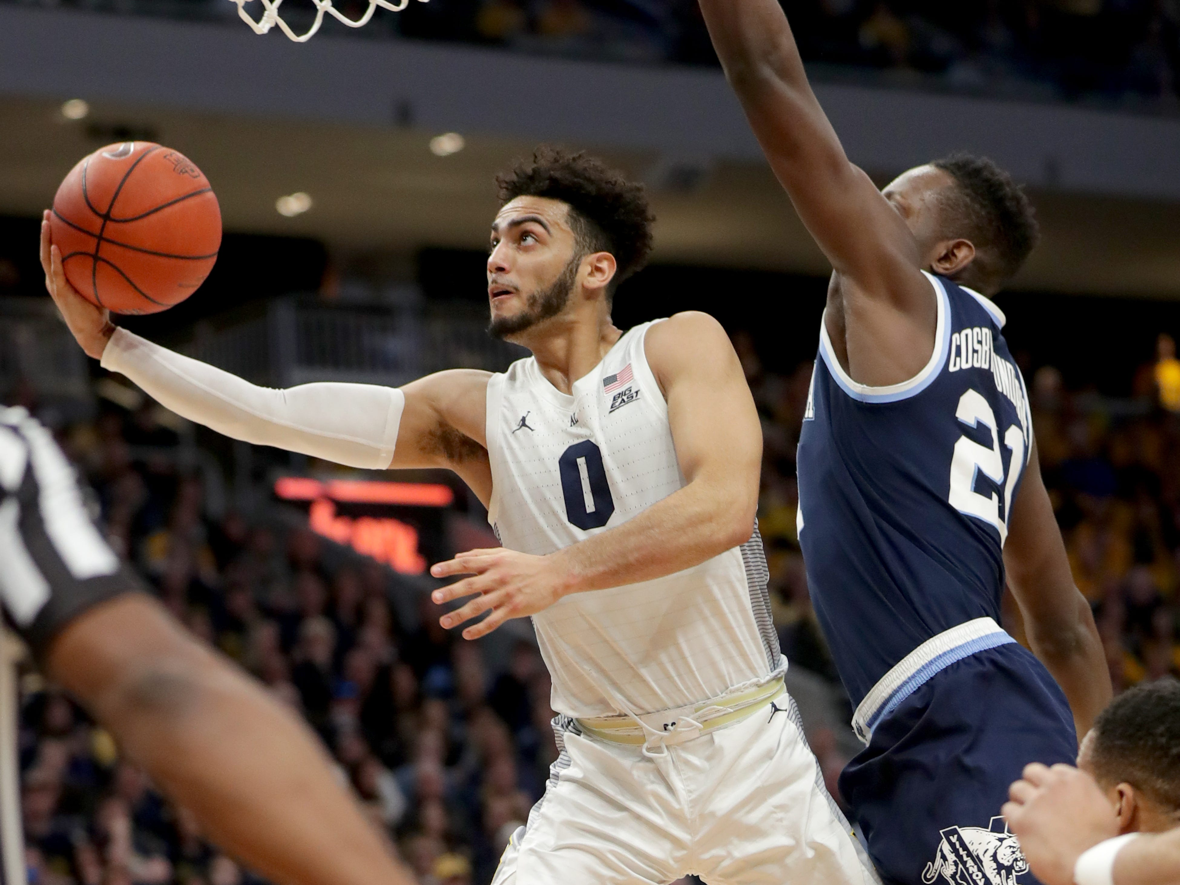 Marquette guard Markus Howard drives to the basket past  Villanova's Dhamir Cosby-Roundtree.