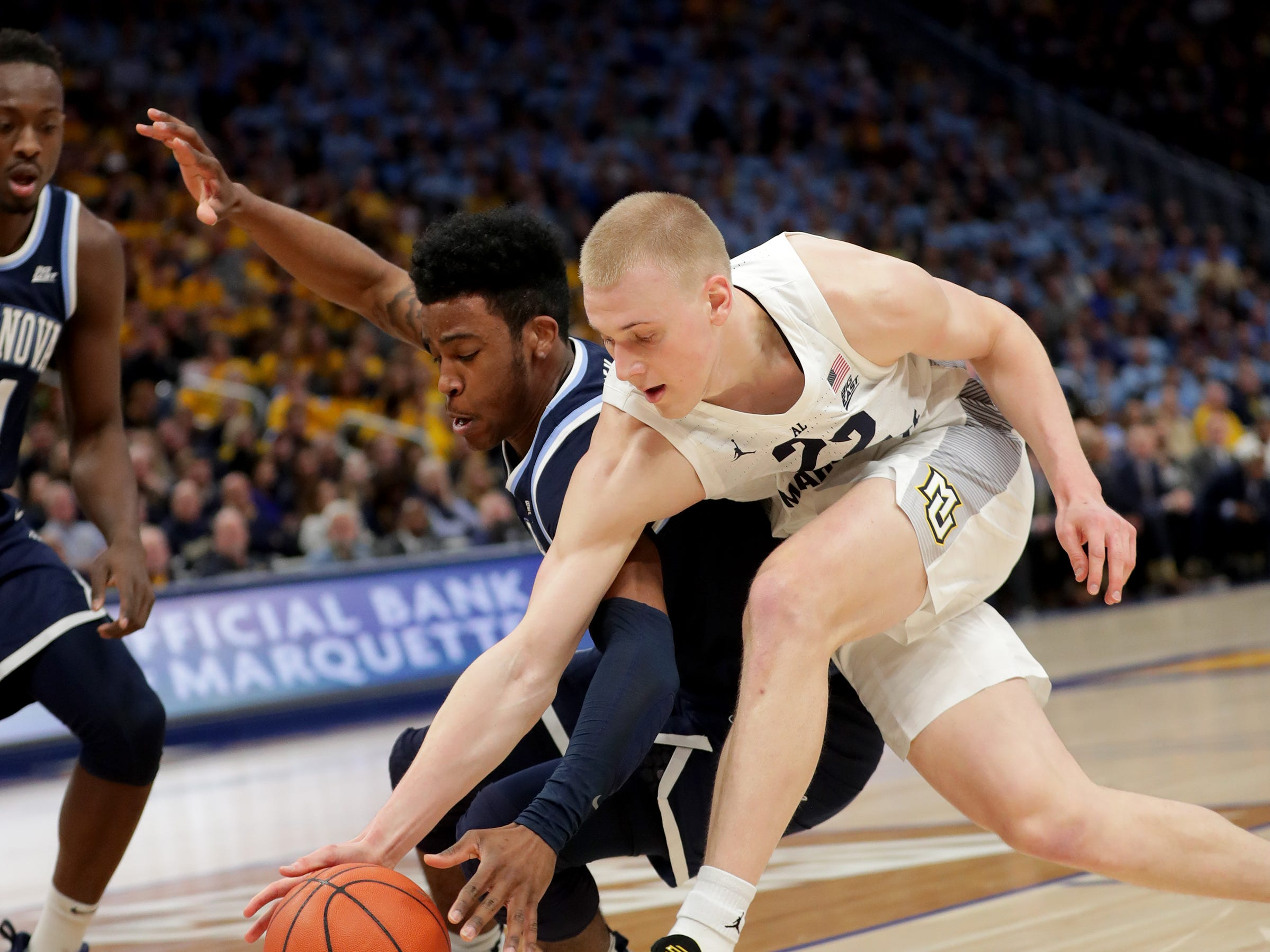 Marquette forward Joey Hauser battles for a loose ball with Villanova  forward Dhamir Cosby-Roundtree.