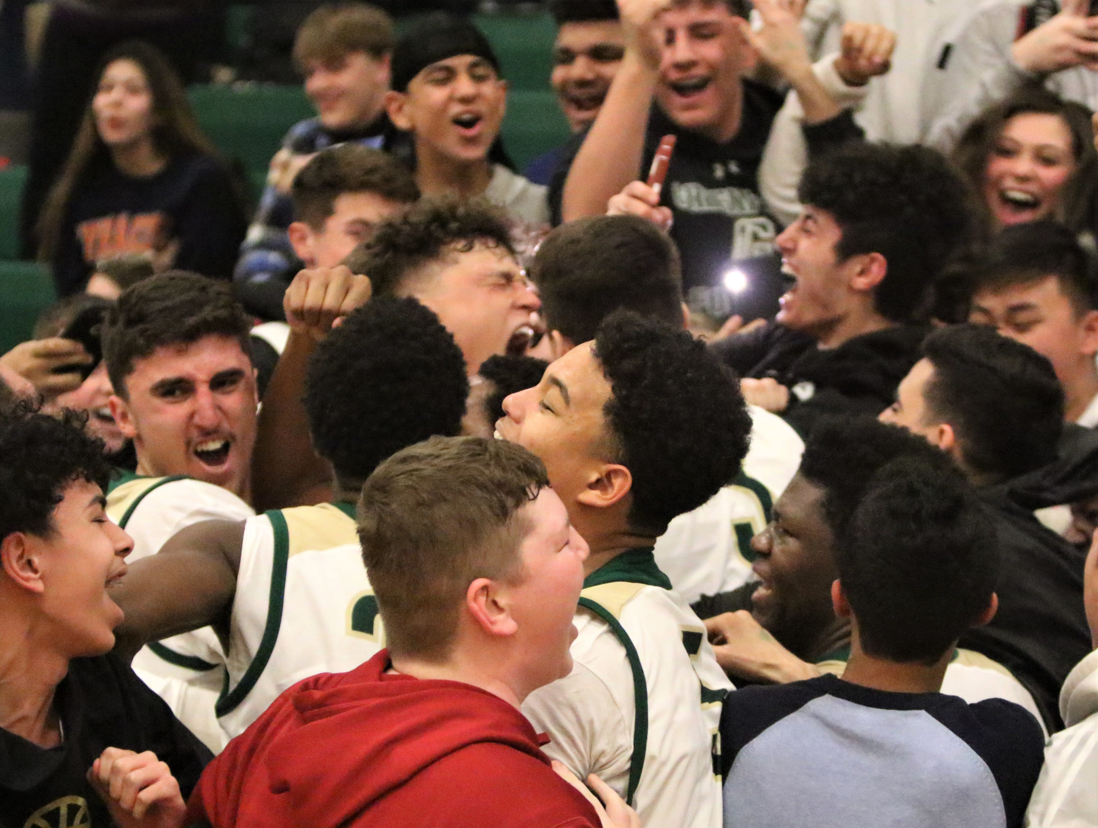 Greenfield players are mobbed by the team's student section after a 68-66 overtime win over Milwaukee Lutheran on Feb. 8, 2019.