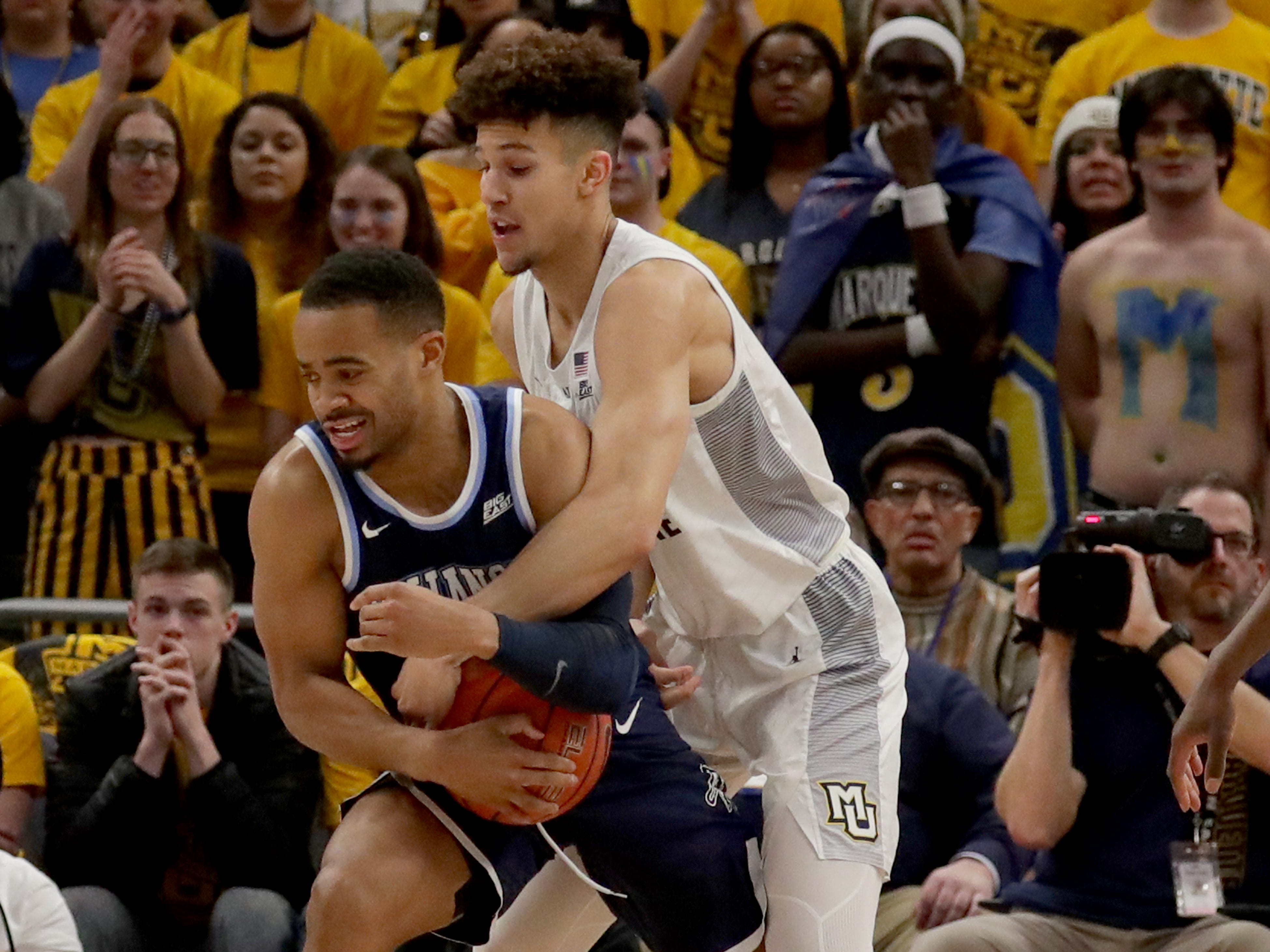 Marquette's Brendan Bailey tries to tie up Villanova's Phil Booth on Saturday.