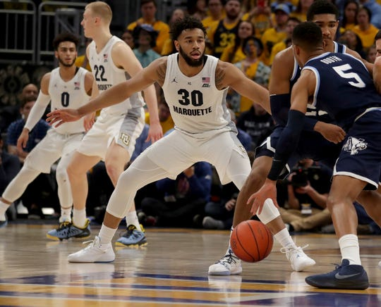 Marquette  forward Ed Morrow makes a defensive switch to guard Villanova's Phil Booth.