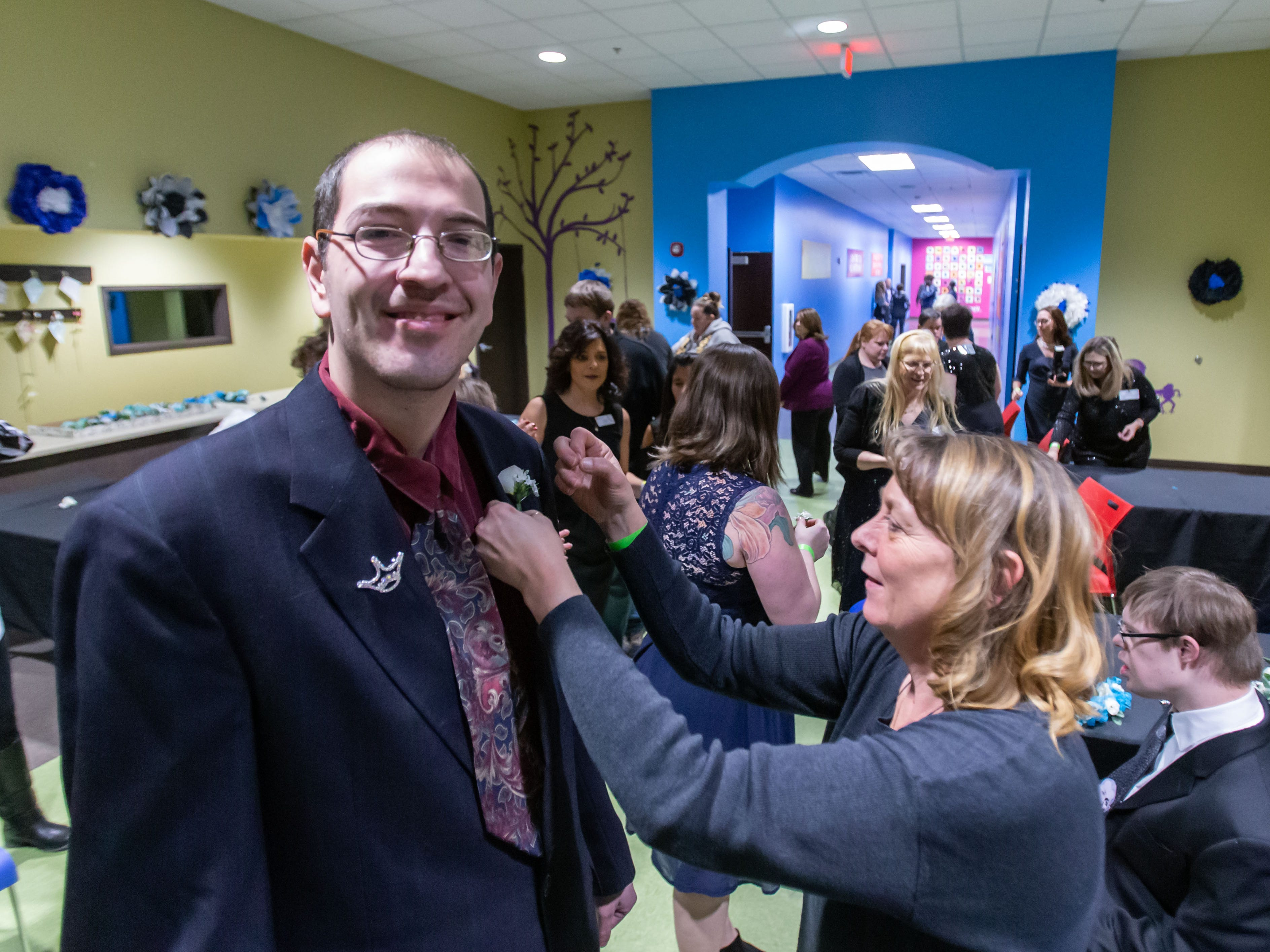 Nicolas C. is fitted with a boutonniere by volunteer Holly Soto during the Night to Shine Prom hosted by Brooklife Church in Mukwonago on Friday, Feb. 8, 2019. Every guest of Night to Shine receives the royal treatment, including hair and makeup, limousine rides, corsages and boutonnieres, a catered dinner, karaoke and dancing, all leading up to the moment when each guest is crowned king or queen of the prom.
