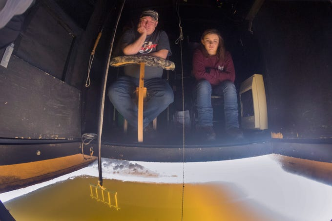 Ken Krueger and his daughter, Nicole, sit in the shack during the opening day of sturgeon spearing Saturday, Feb. 9, 2019, in Fond du Lac, Wis. The Winnebago System contains one of the largest and best-managed sturgeon populations in the world.