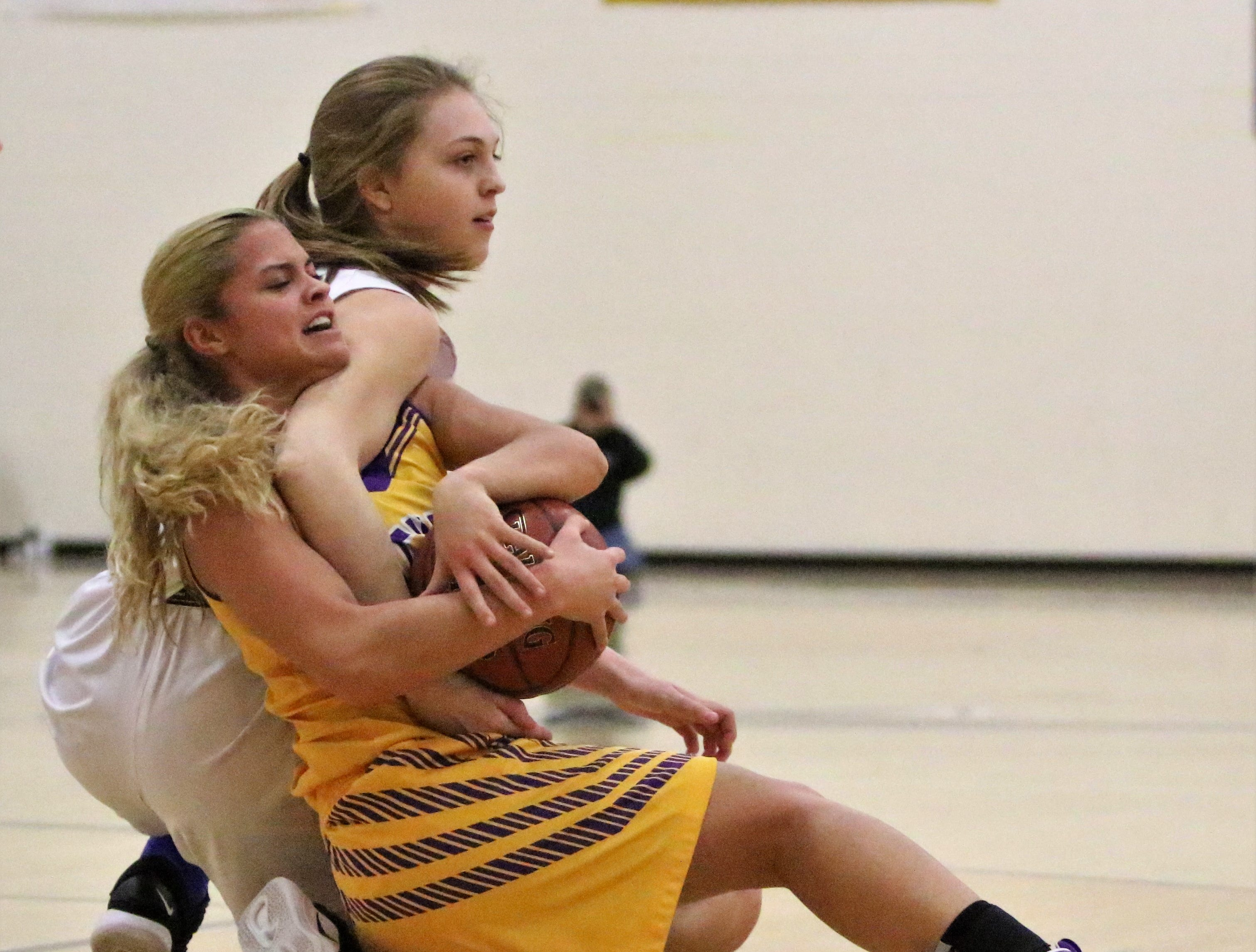 Cudahy guard Camryn Kratt (front) ties up a loose ball against Whitnall on Feb. 8, 2019.