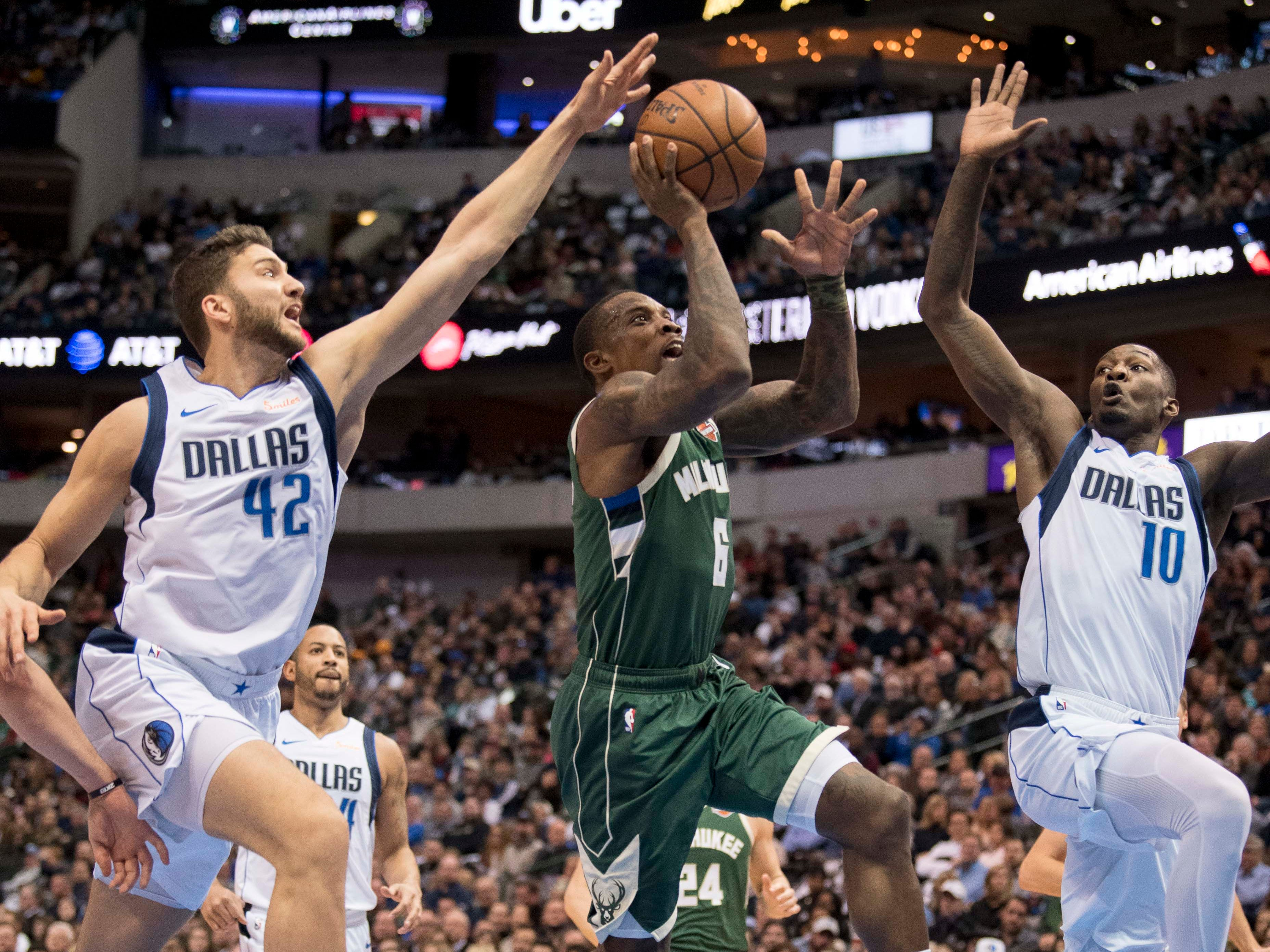Bucks guard Eric Bledsoe goes up for a shot between Maxi Kleber and Dorian Finney-Smith on a drive to the hoop during the second quarter Friday.