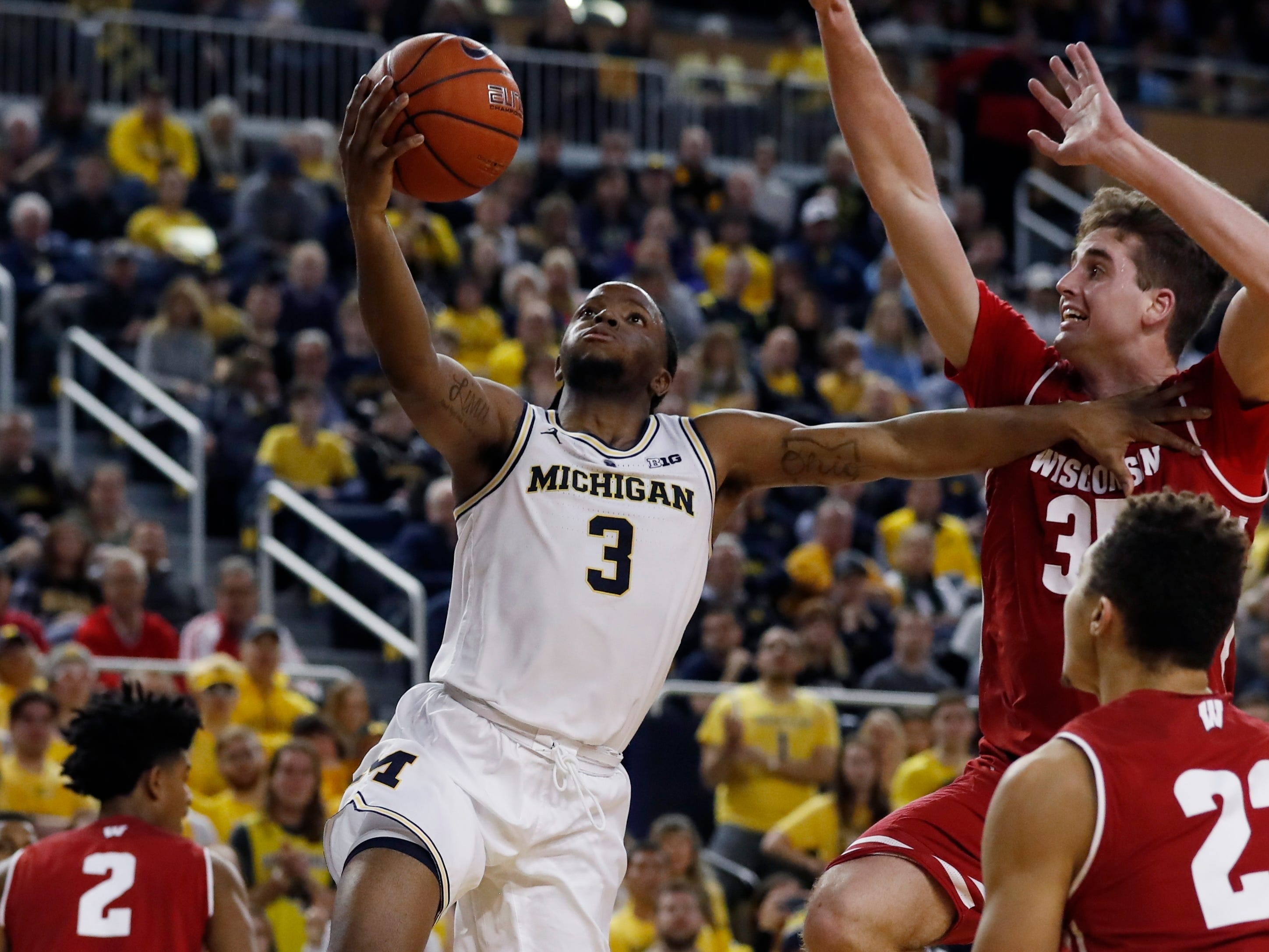Michigan guard Zavier Simpson gets past Wisconsin defenders for a layup.