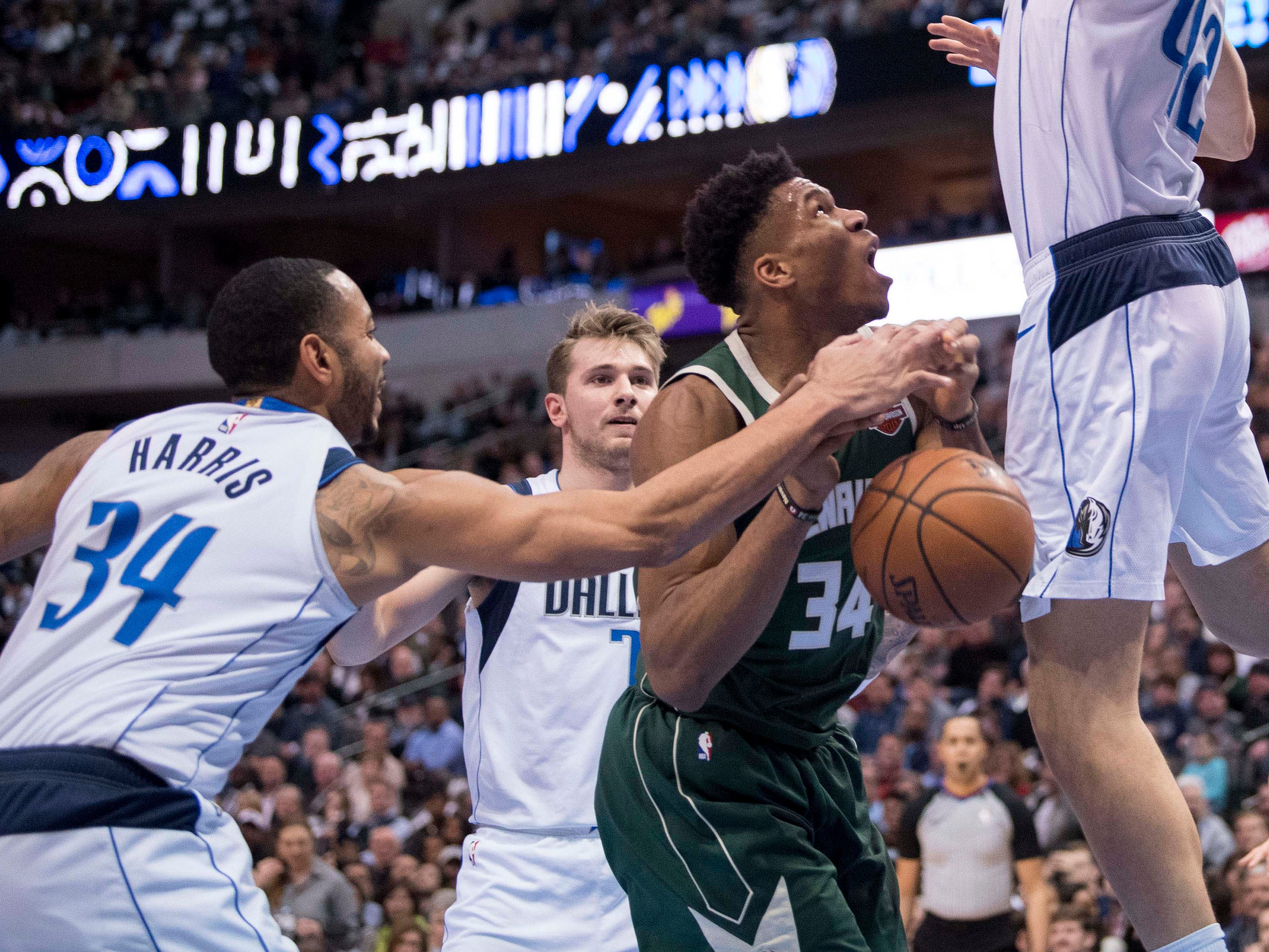 Mavericks guard Devin Harris, who starred at Wauwatosa East and Wisconsin, reaches in a fouls Bucks forward Giannis Antetokounmpo during the second quarter on Friday.
