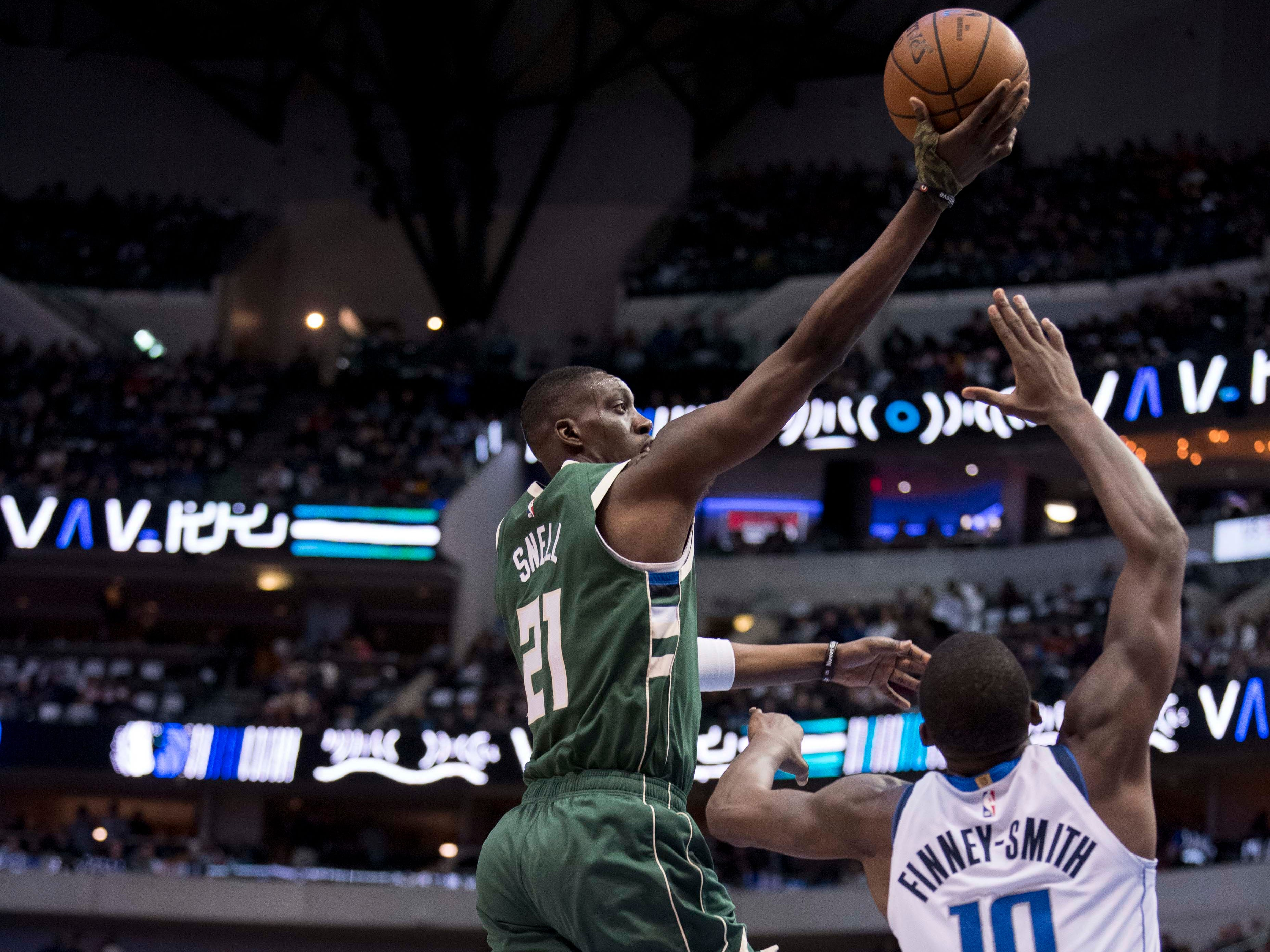 Bucks guard Tony Snell soars past Mavericks forward Dorian Finney-Smith as he goes in for a layup during the second quarter Friday night.
