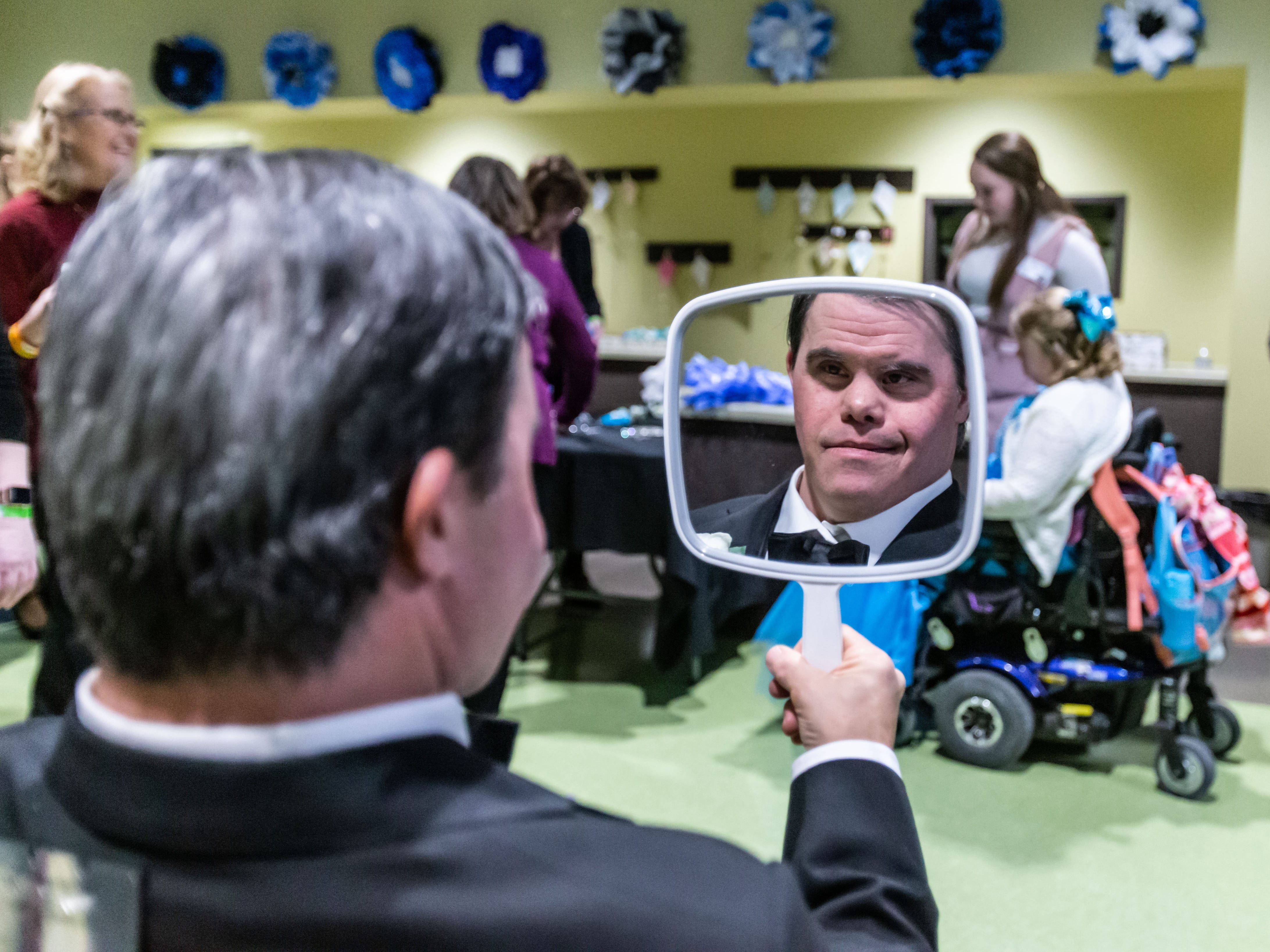 Michael G. checks his appearance after receiving the royal treatment during the Night to Shine Prom hosted by Brooklife Church in Mukwonago on Friday, Feb. 8, 2019. Every guest of Night to Shine receives the royal treatment, including hair and makeup, limousine rides, corsages and boutonnieres, a catered dinner, karaoke and dancing, all leading up to the moment when each guest is crowned king or queen of the prom.