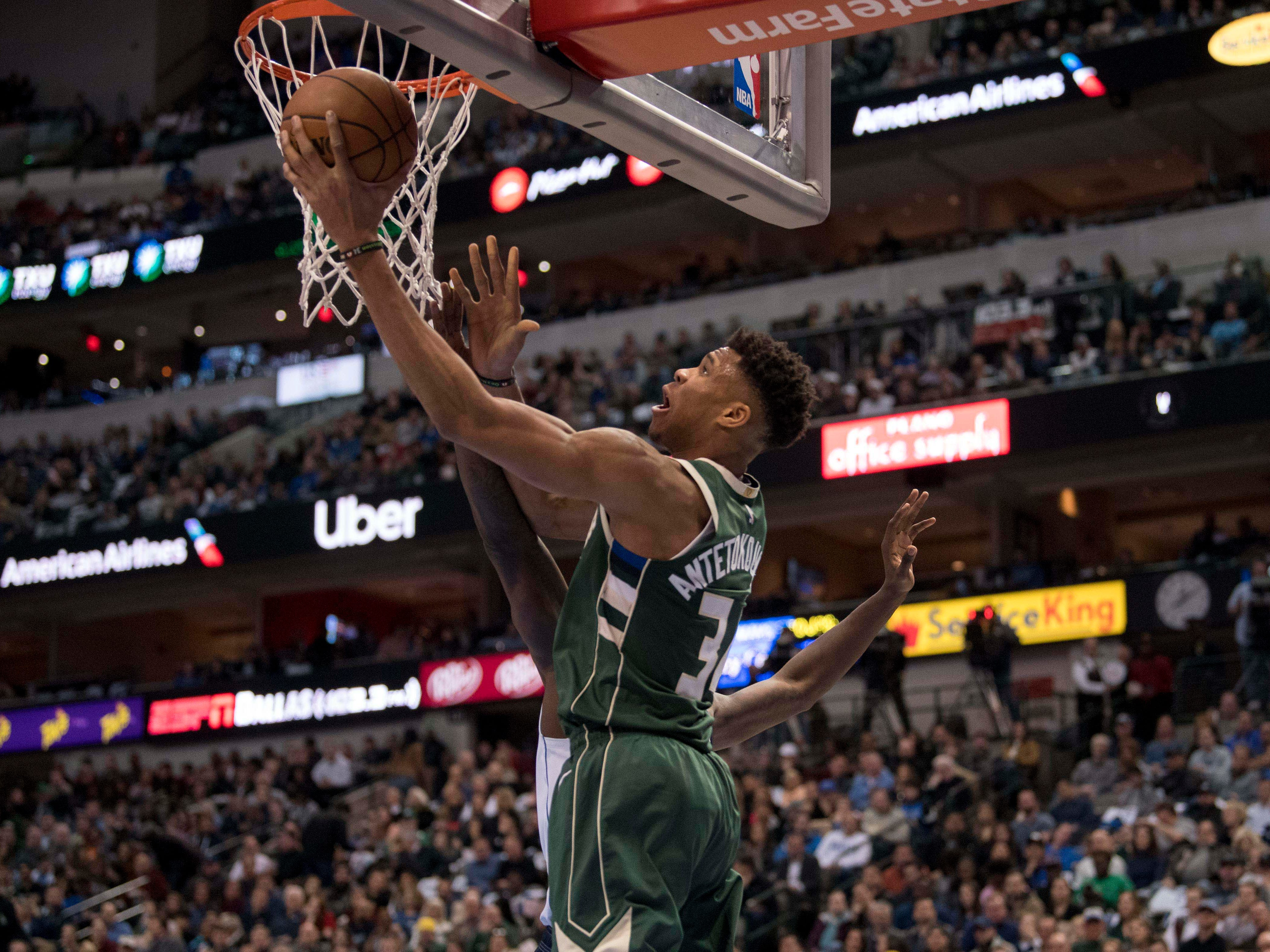 Bucks forward Giannis Antetokounmpo goes up for a reverse dunk during the second quarter against the Mavericks on Friday night.