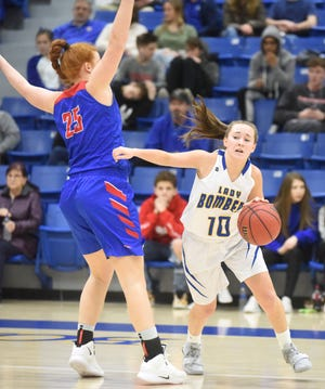 Mountain Home's Payton Huskey dribbles around Paragould's Zoey Beasley during the Lady Bombers' 30-16 victory Friday night.