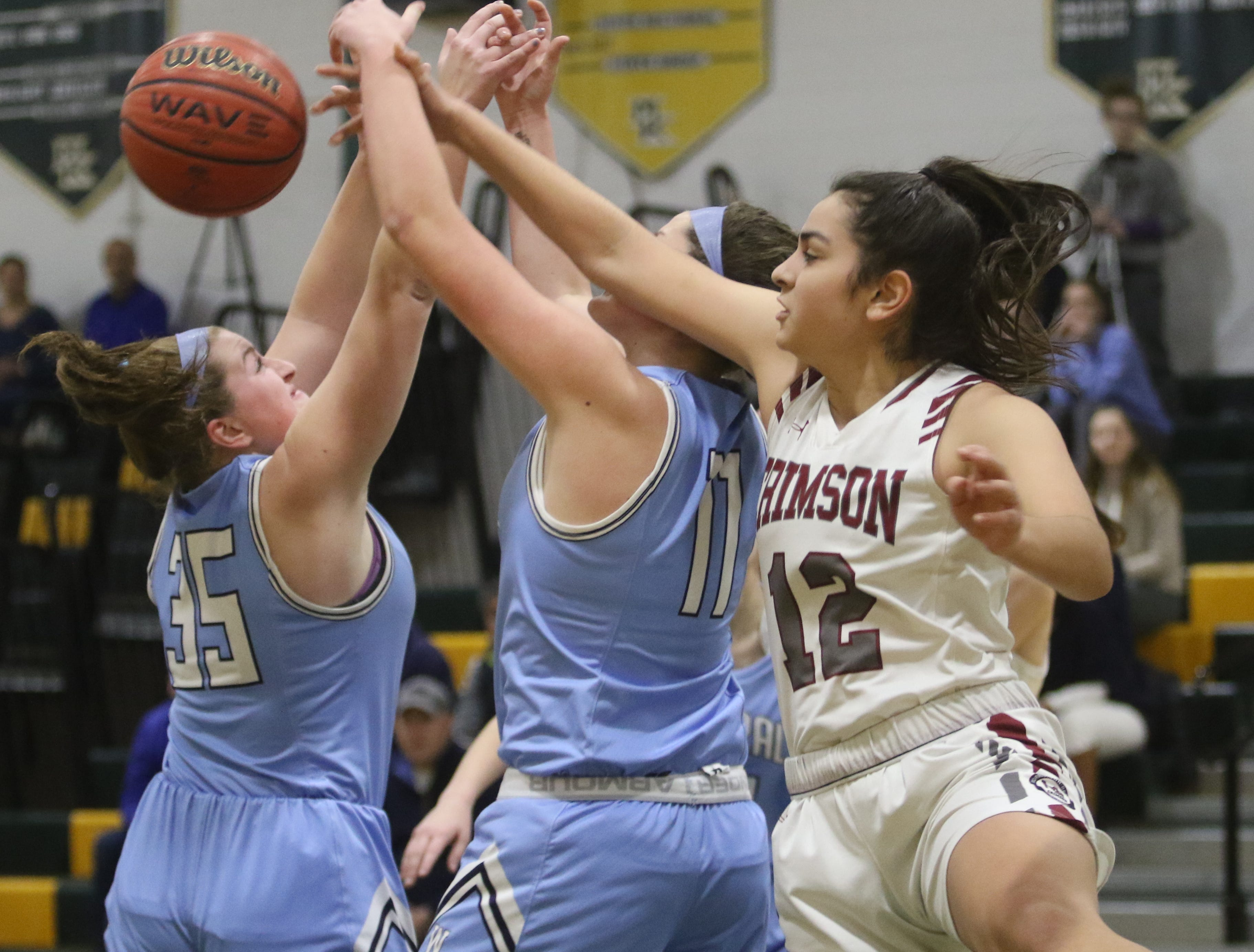 Olivia Schlok and Caroline Coleman of West Morris keep the rebound away from Addisyn Ibrahim of Morristown Beard in the first half.
