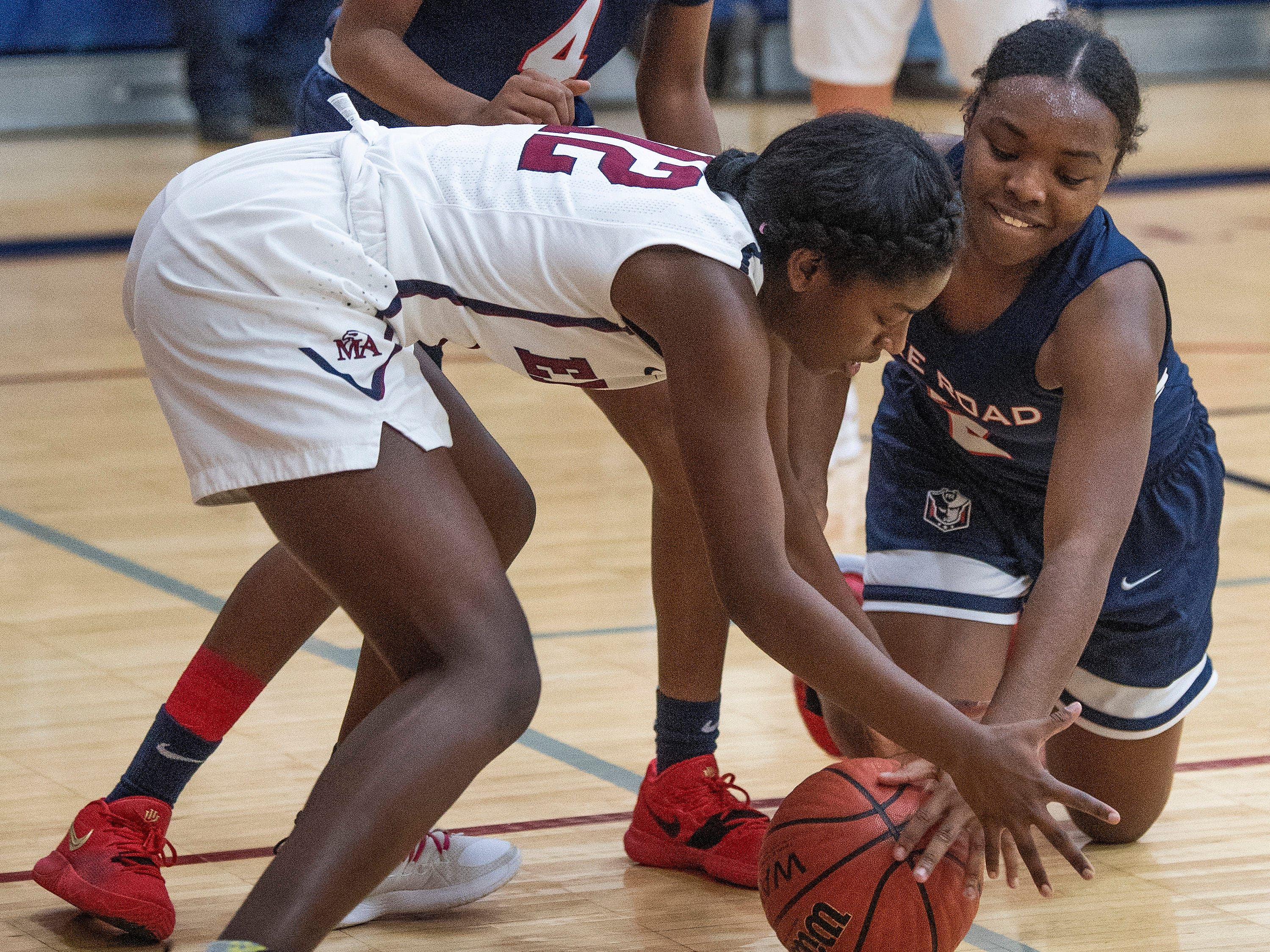 Montgomery Academy's Katherine Yelverton (12) and Pike Road's Jakhiah Lewis (2) go after a loose ball on the MA campus in Montgomery, Ala., on Friday February 8, 2019.