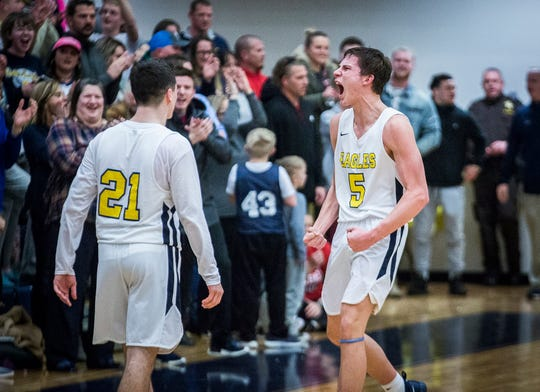 Delta's Josh Bryan, right, celebrates defeating New Castle during their game at Delta High School Friday, Feb. 8, 2019.