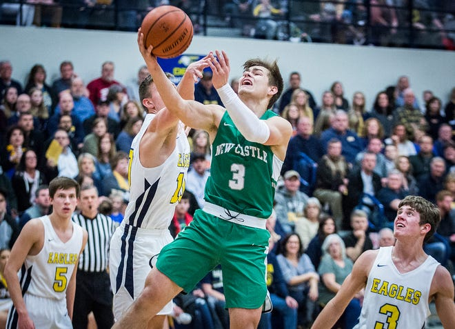New Castle's Luke Bumbalough fights past Delta's defense during their game at Delta High School Friday, Feb. 8, 2019.