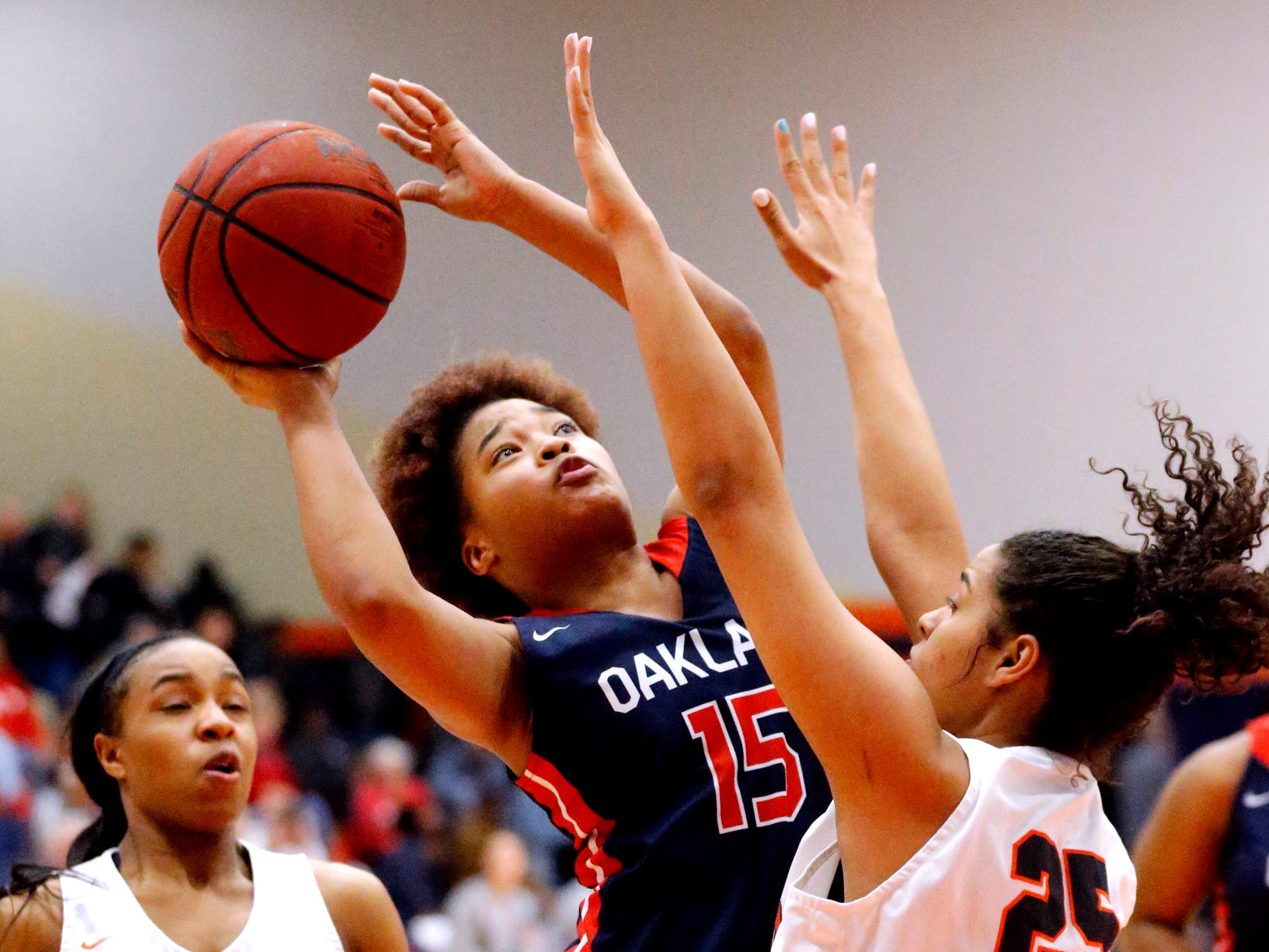 Oakland's Janiyah Riley (15) shoots the ball as Blackman's Aaliyah Green (25) defends her on Friday, Feb. 8, 2019.