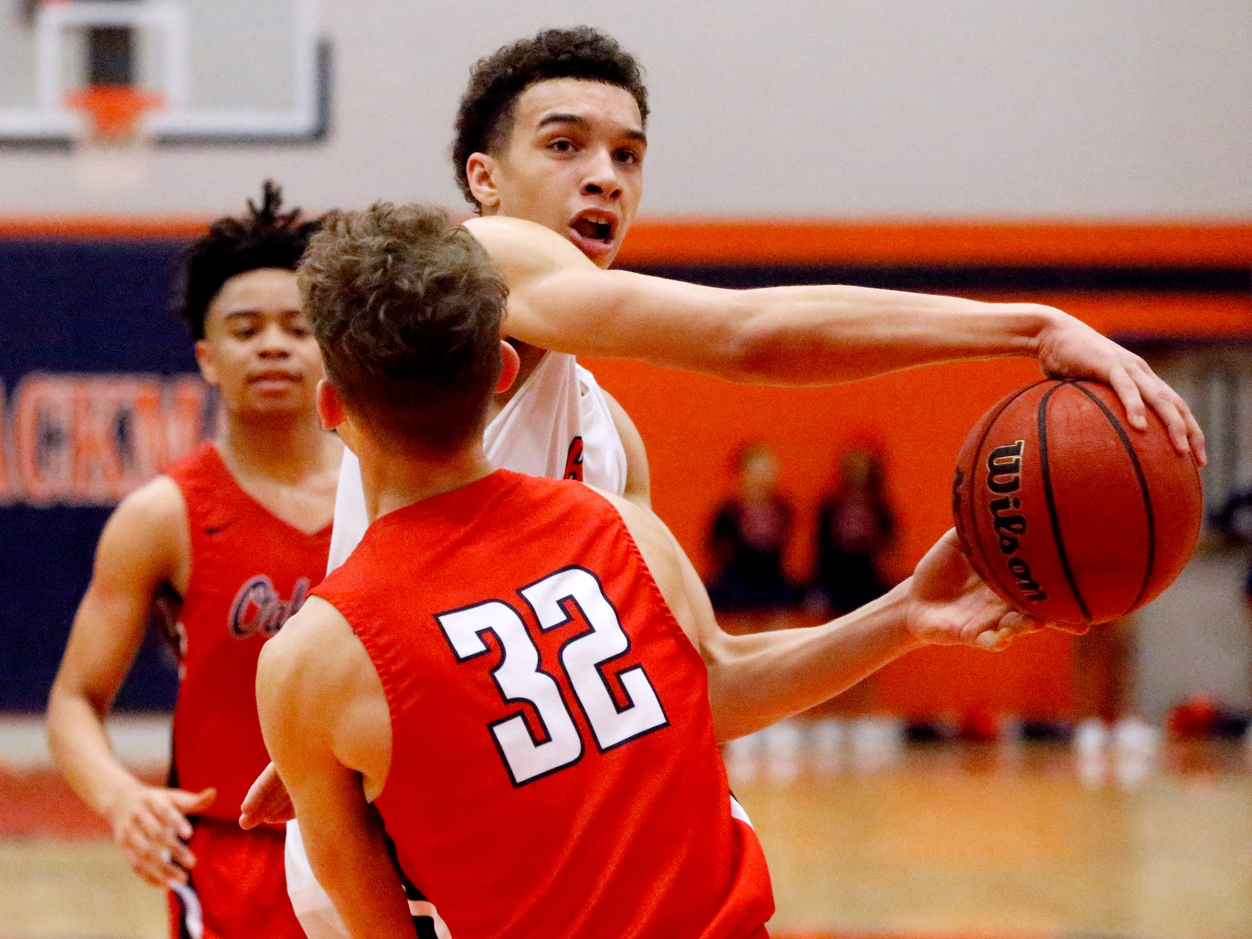 Blackman's Jalen Page (15) tries to pass the ball around Oakland's Carter Baugh (32) on Friday, Feb. 8, 2019.