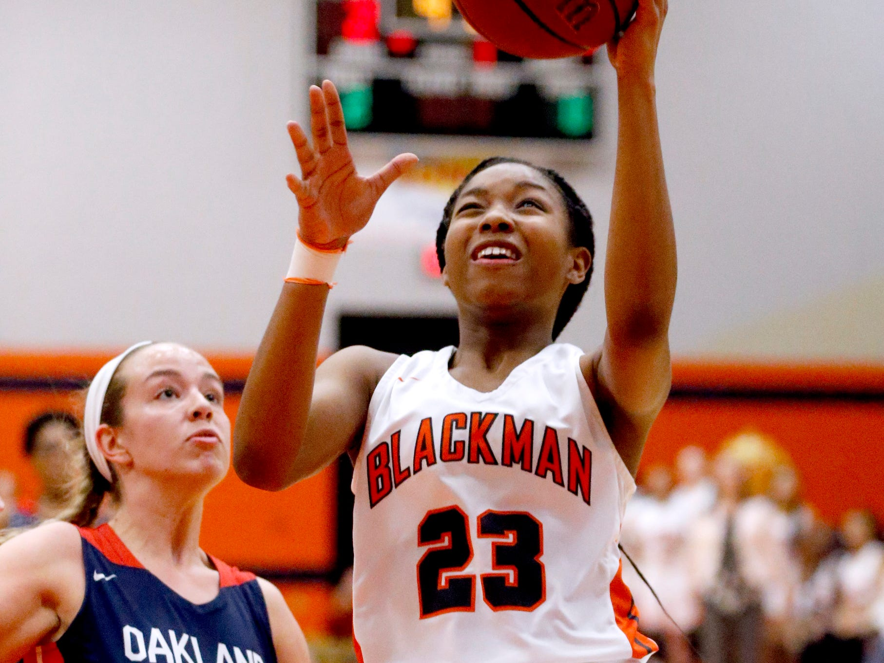 Blackman's Iyana Moore (23) shoots the ball as Oakland's Olivia Perry (24) defends her on Friday, Feb. 8, 2019.