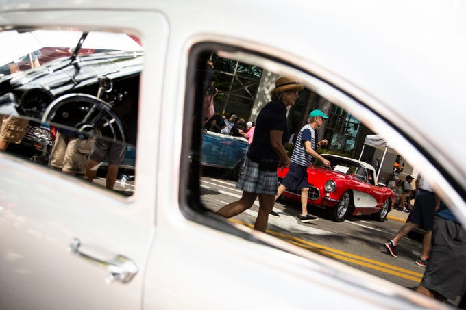 A red 1957 Chevrolet Corvette is reflected in the window of a 1950 Ford Business Coupe during the 15th annual Cars on 5th event, organized by the Naples Chapter of the Ferrari Club of America, on 5th Avenue South in Naples, on Saturday, February 9, 2019. Proceeds from the event go to St. MatthewÕs House, which helps people who are homeless, hungry, or recovering from substance abuse.