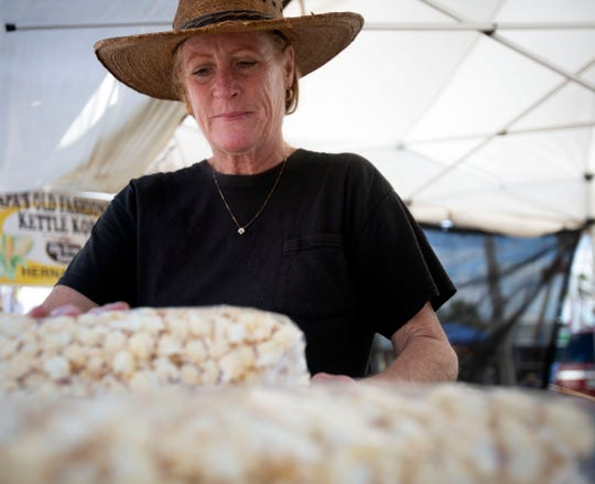 Quinn Maiocco prepares bags of kettle corn popcorn during the 49th annual Everglades City Seafood Festival on Saturday in Everglades City.