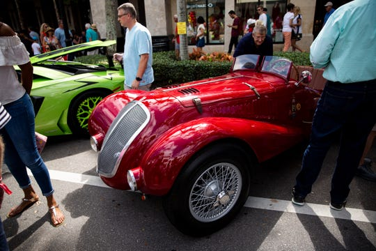 Car show attendees look at a 1937 Fiat Roadster on display during the 15th annual Cars on 5th event, organized by the Naples Chapter of the Ferrari Club of America, on 5th Avenue South in Naples, on Saturday, February 9, 2019. Proceeds from the event go to St. MatthewÕs House, which helps people who are homeless, hungry, or recovering from substance abuse.