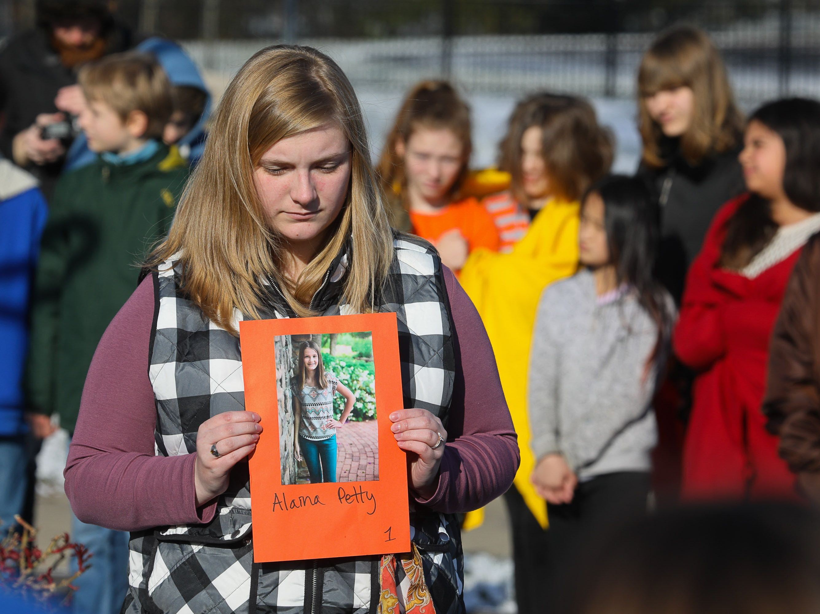 ALAINA PETTY. Kelly Golway holds a photo of Alaina Petty, one of the 17 killed at Marjory Stoneman Douglas High School, during a protest at Walden School in Louisville, Kentucky. Mar. 14, 2018