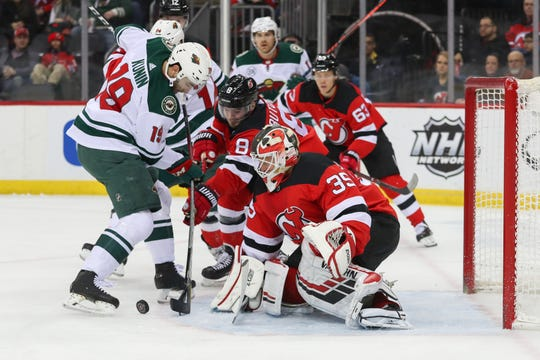 Feb 9, 2019; Newark, NJ, USA; Minnesota Wild center Luke Kunin (19) looks for the puck after a save by New Jersey Devils goaltender Cory Schneider (35) during the first period at Prudential Center.