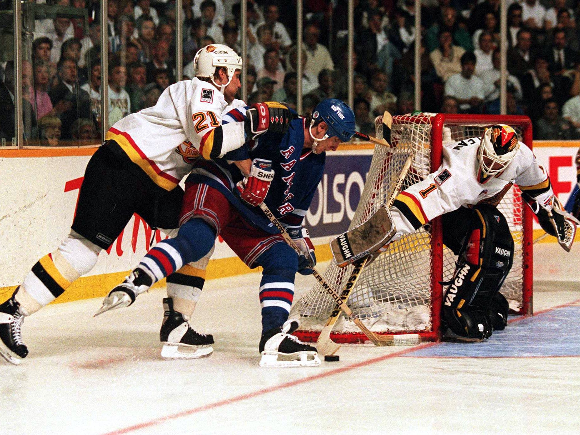 7 Jun 1994: RANGERS FORWARD STEVE LARMER IS MANHANDLED BY CANUCKS DEFENSEMAN JYRKI LUMME WHILE GOALTENDER KIRK MCLEAN POKE-CHECKS AWAY THE PUCK DURING THE THIRD OF GAME FOUR OF THE STANLEY CUP FINALS IN VANCOUVER, BRITISH COLUMBIA. LUMME WAS CALLED FOR A PENALTY